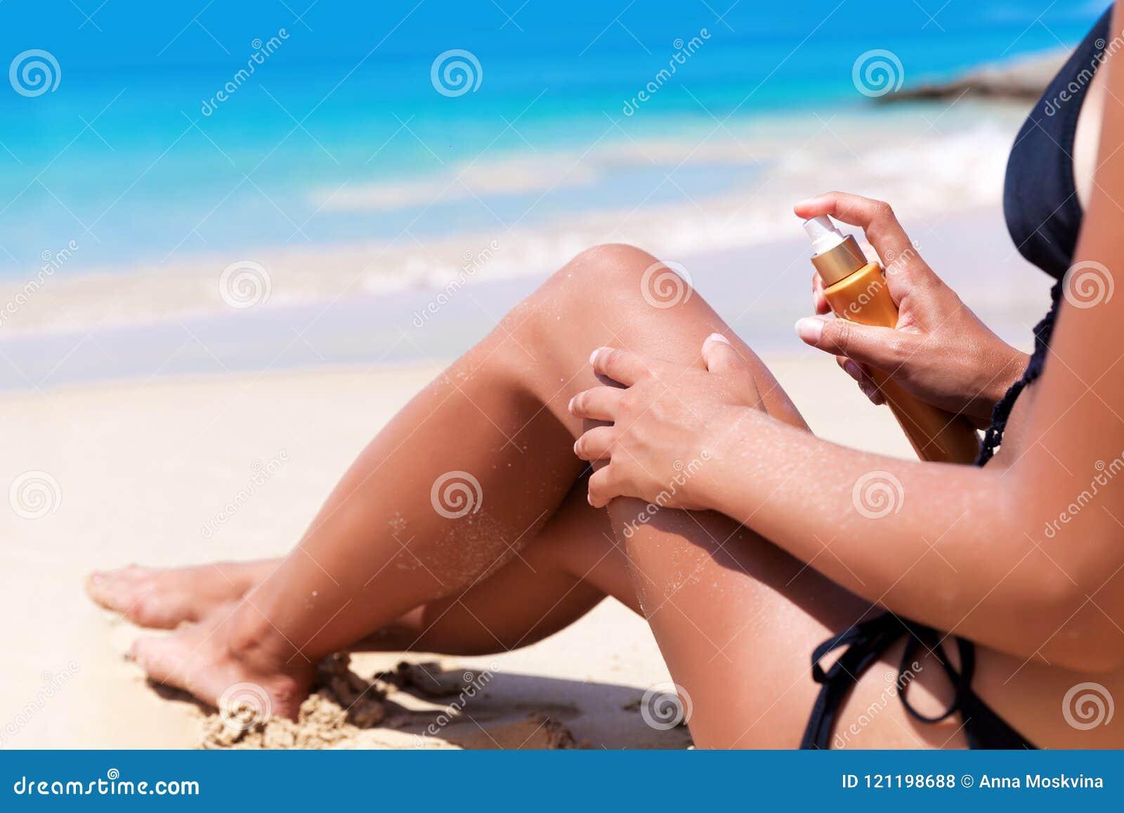 Femme blonde assez mince de jeunes avec de la crème de protection solaire sur la plage
