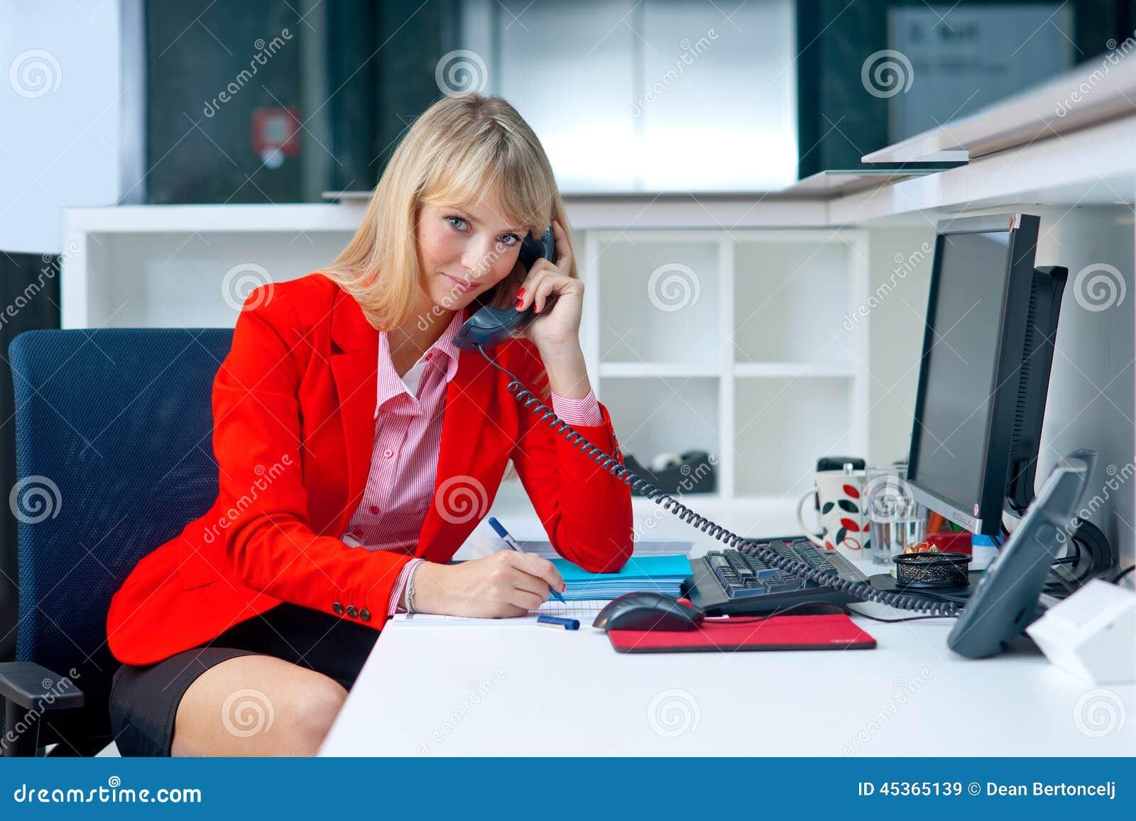 Femme blonde attirante dans le bureau parlant au téléphone