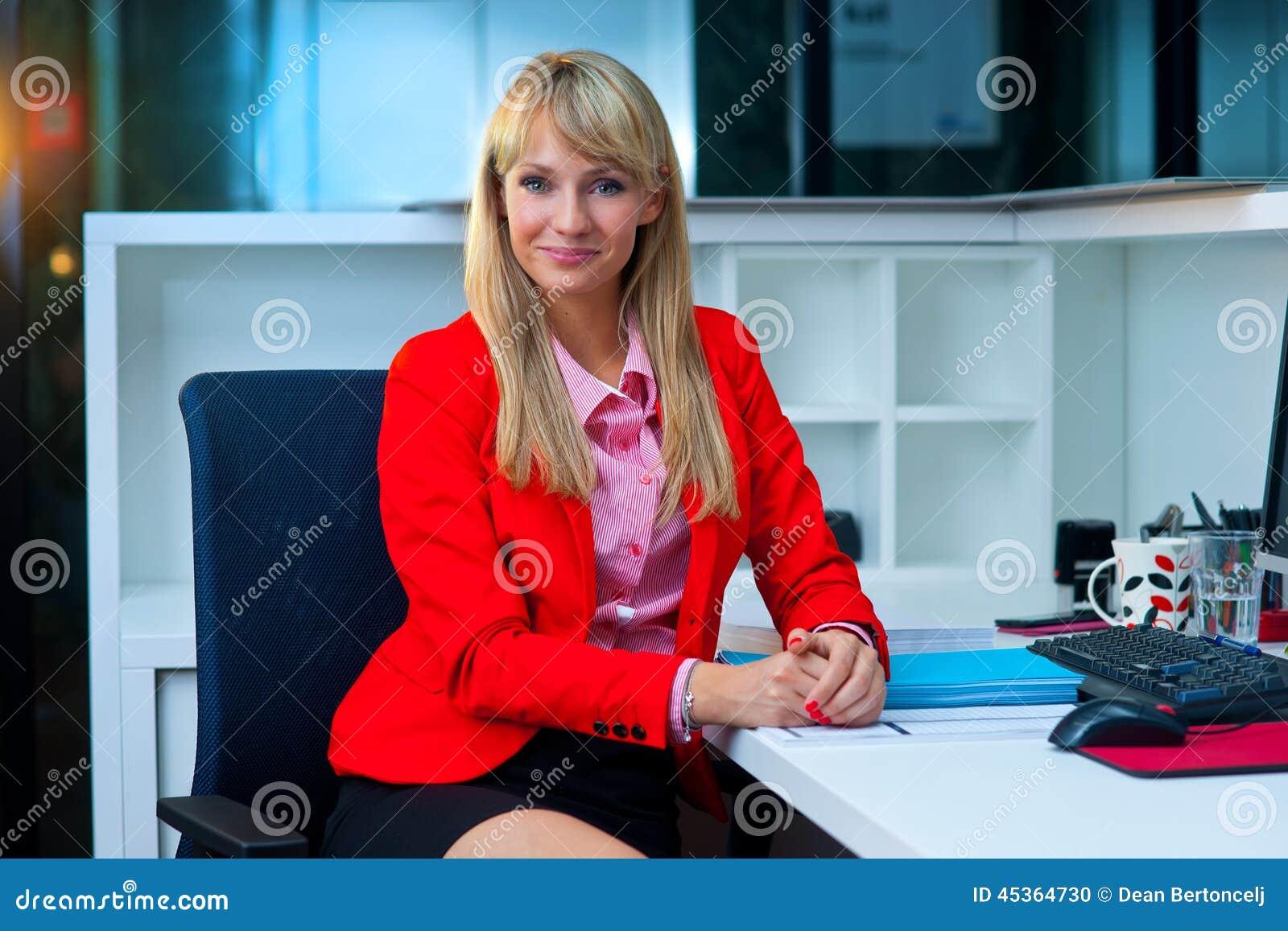 Femme blonde attirante dans le sourire de bureau