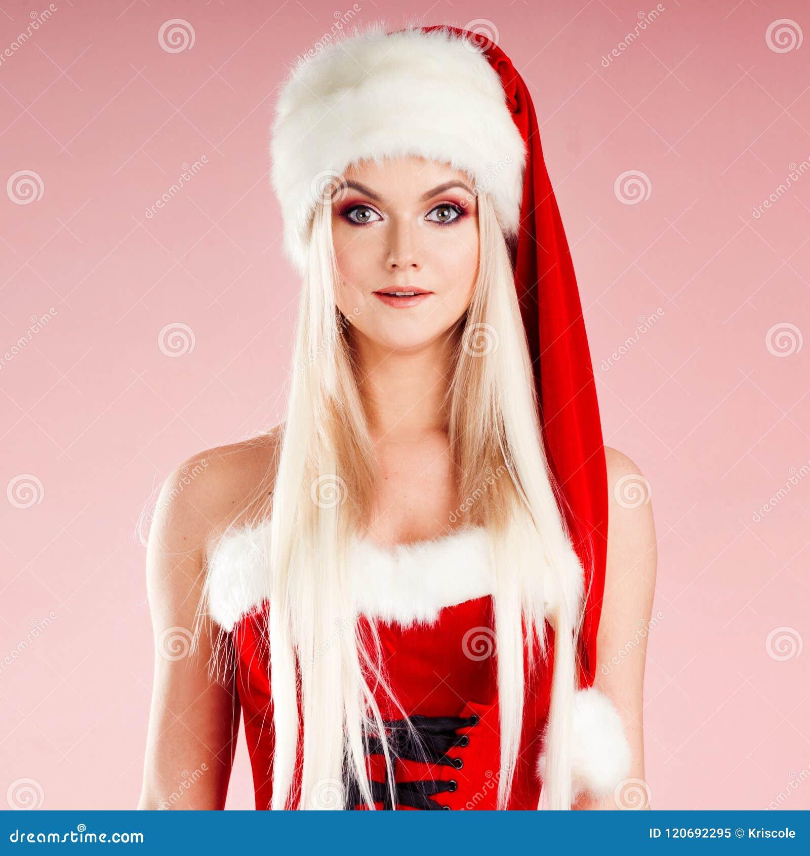 Femme blonde avec du charme et attirante dans un costume de Santa étonné et ravi