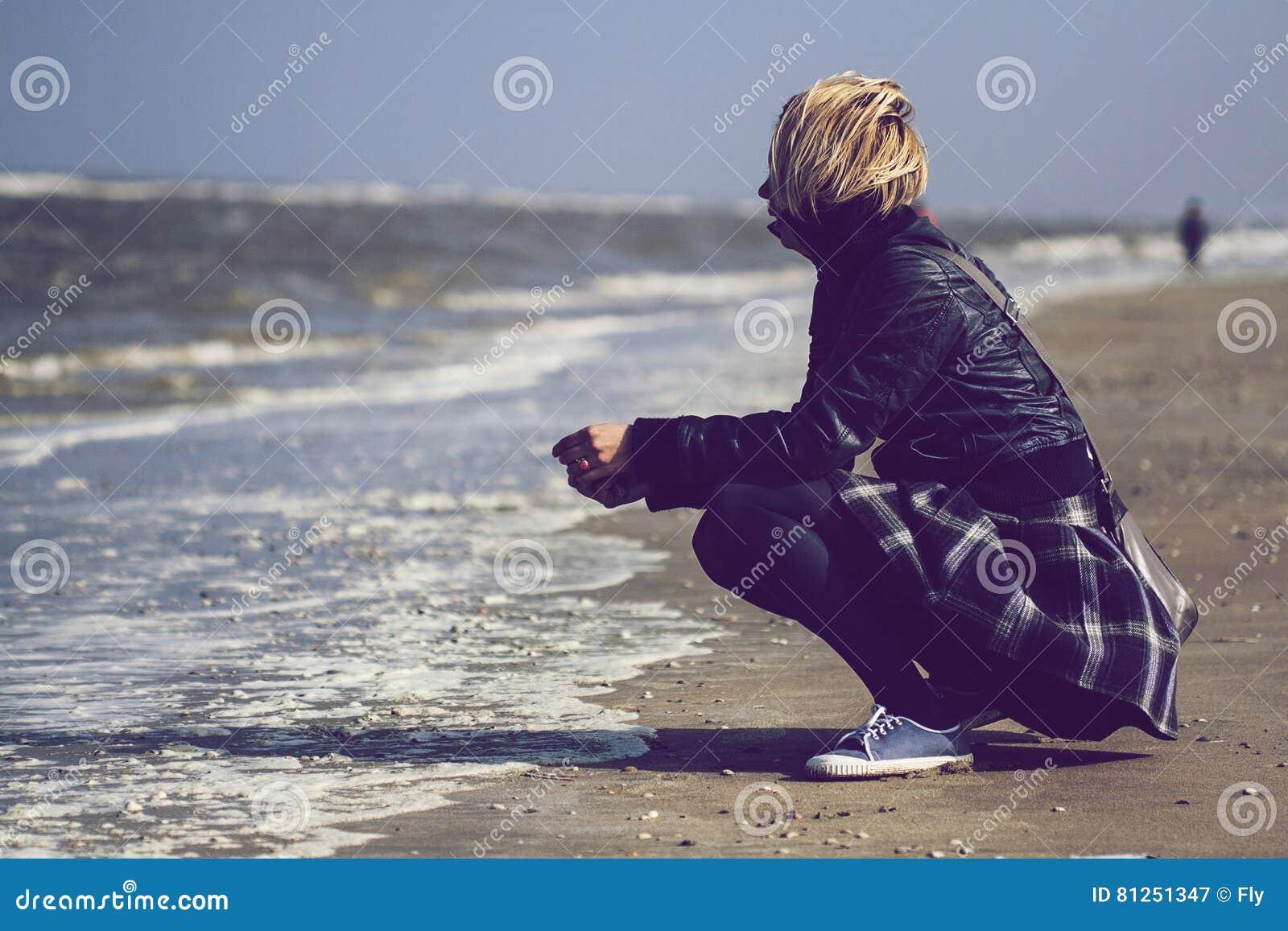 Femme blonde avec la jupe devant l océan