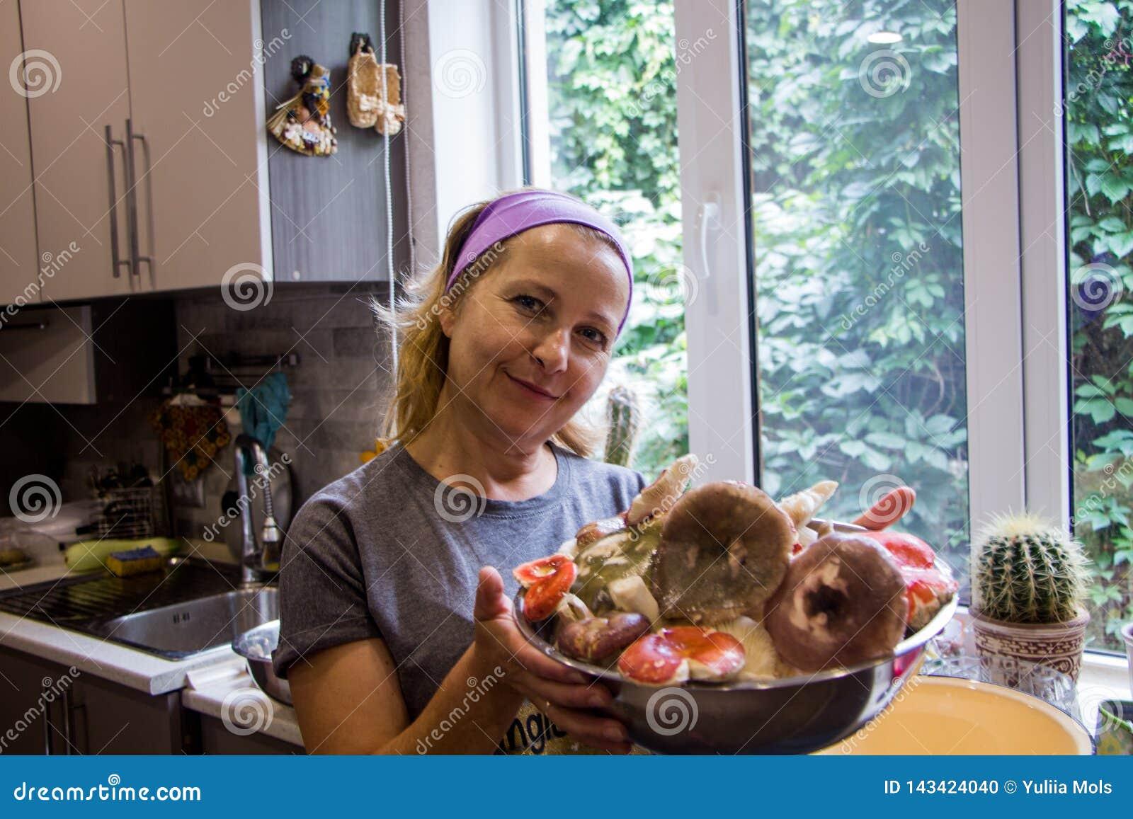 Femme blonde avec un plat de champignon de russula