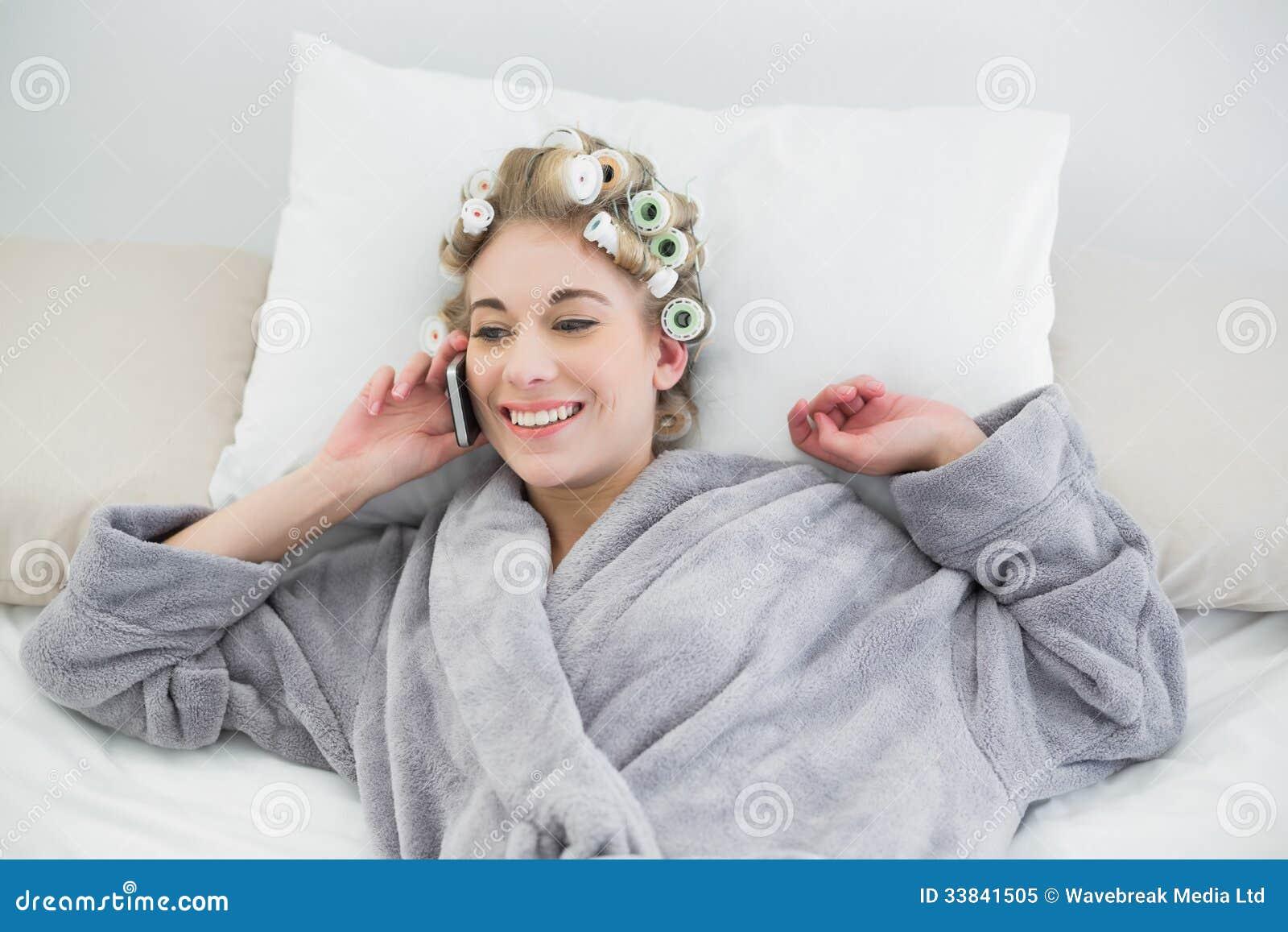 femme blonde d contract e avec plaisir dans des bigoudis de cheveux faisant un appel. Black Bedroom Furniture Sets. Home Design Ideas
