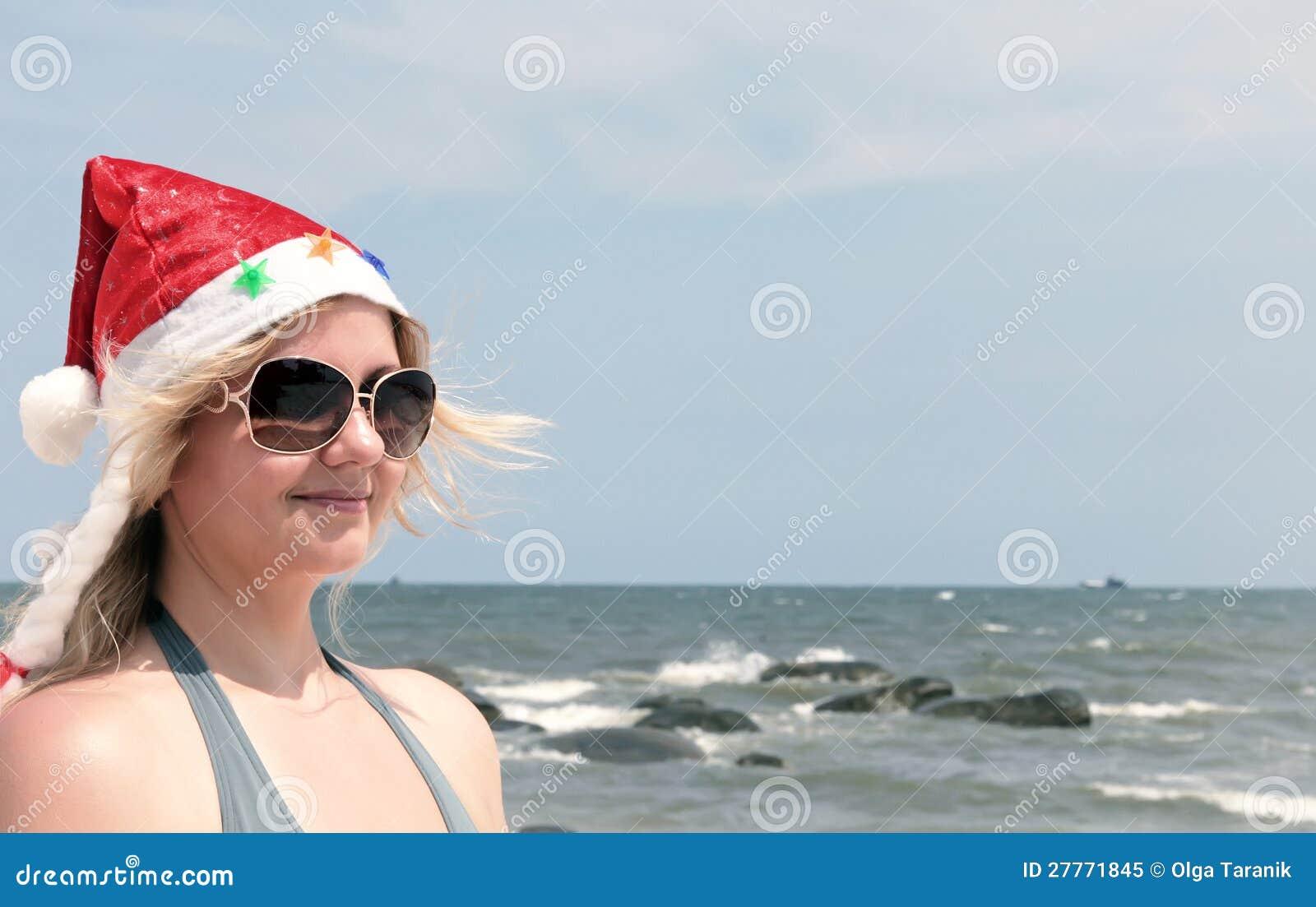 Femme blonde dans le chapeau de Santa sur la plage tropicale