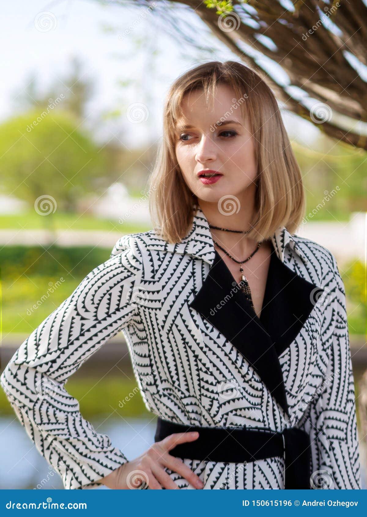 Femme blonde dans un manteau noir et blanc