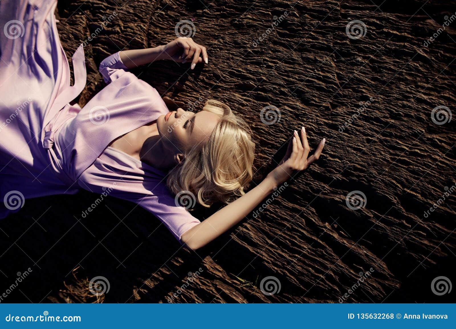 Femme blonde dans une longue robe rose se reposant sur une pierre près de la cascade Beau sourire de longs cheveux magnifiques su