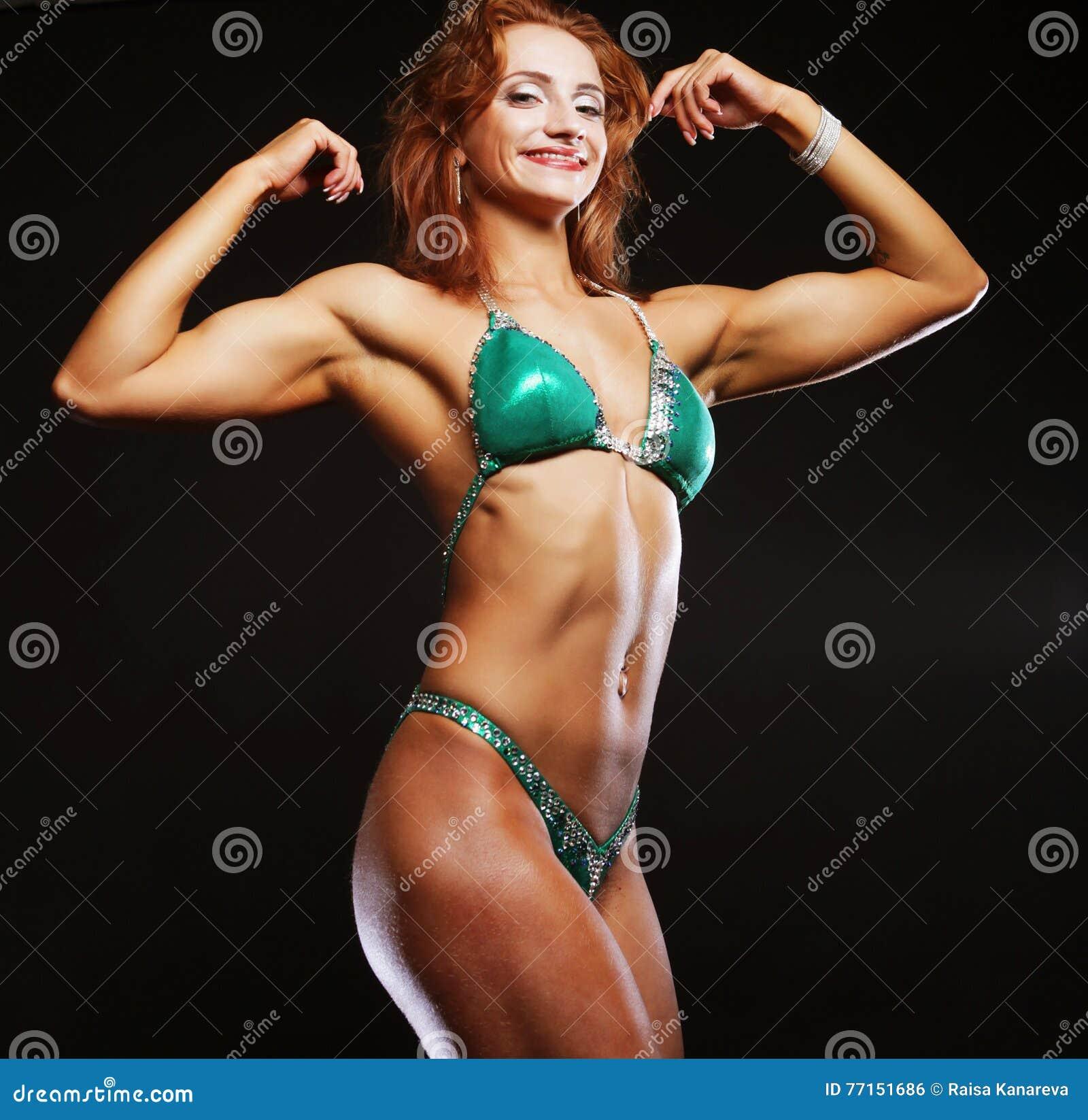 Femme blonde de bodybuilder dans le bikin sur le fond noir
