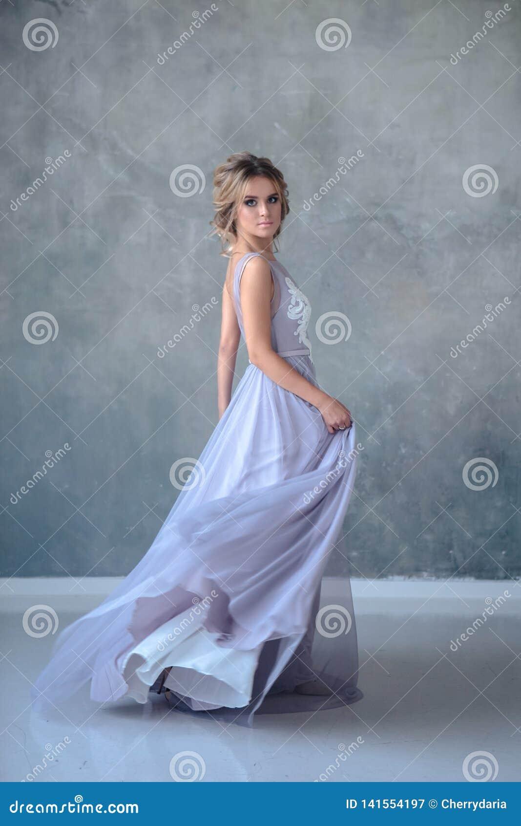 Femme blonde de jeune mariée dans une robe de mariage moderne de couleur avec la coiffure élégante et composer Verticale de beaut