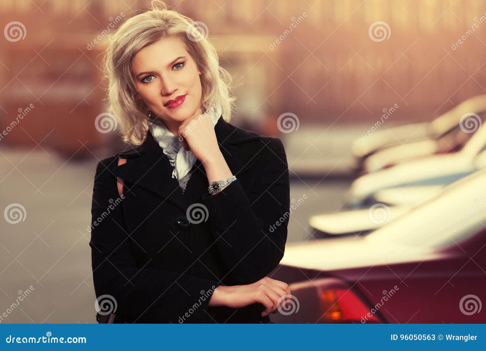 Femme blonde de mode heureuse dans le manteau noir marchant dans la rue de ville