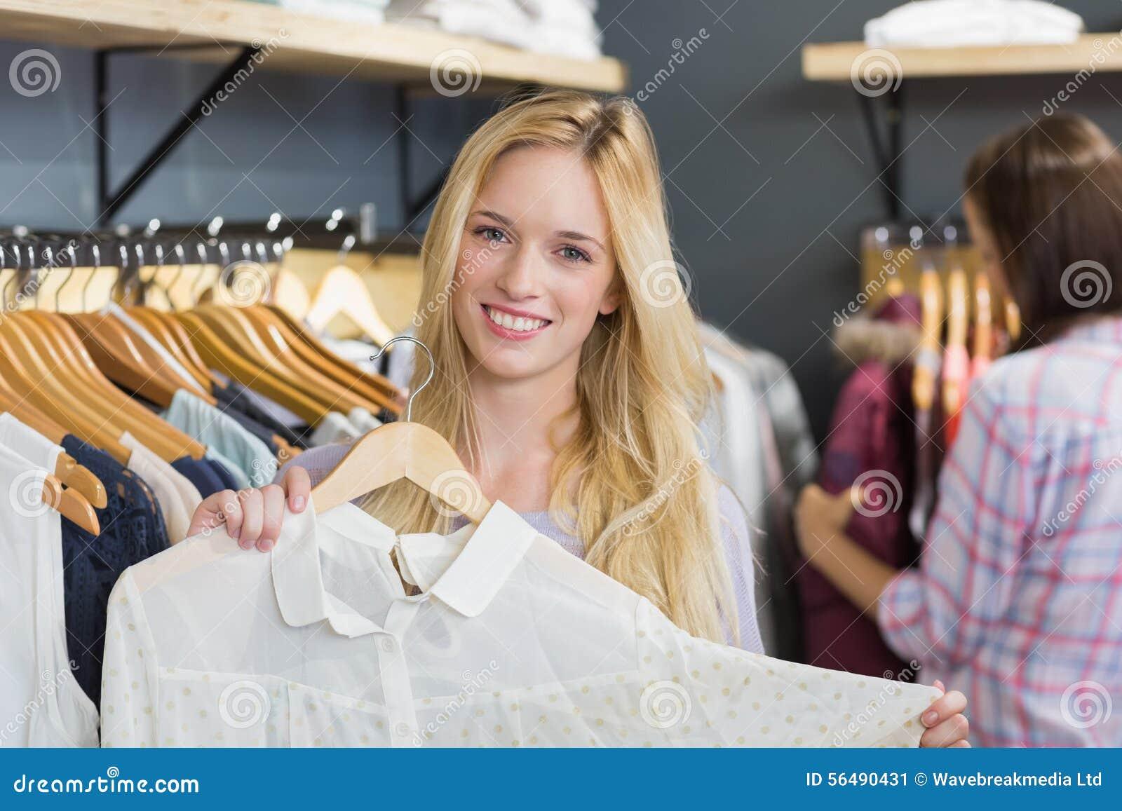Femme blonde de sourire choisissant des vêtements et regarder l appareil-photo
