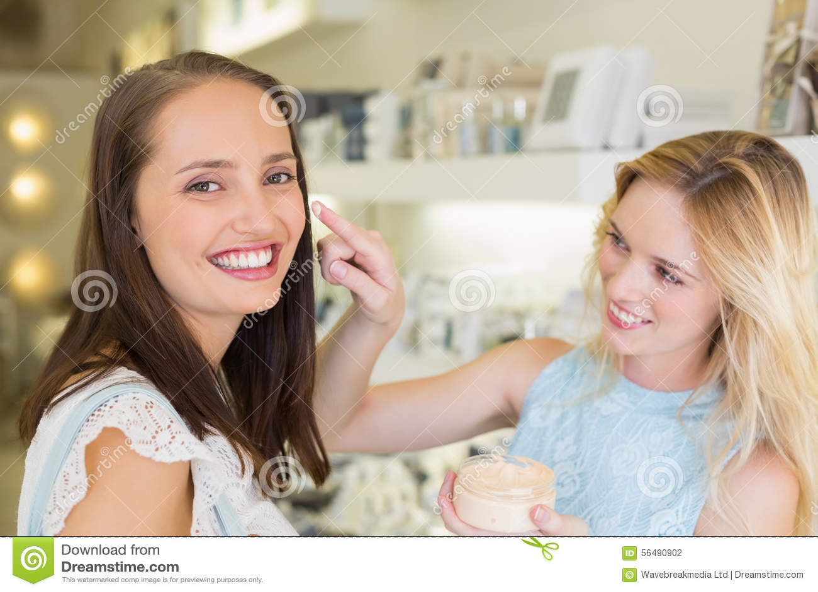 Femme blonde heureuse appliquant les produits cosmétiques sur son ami
