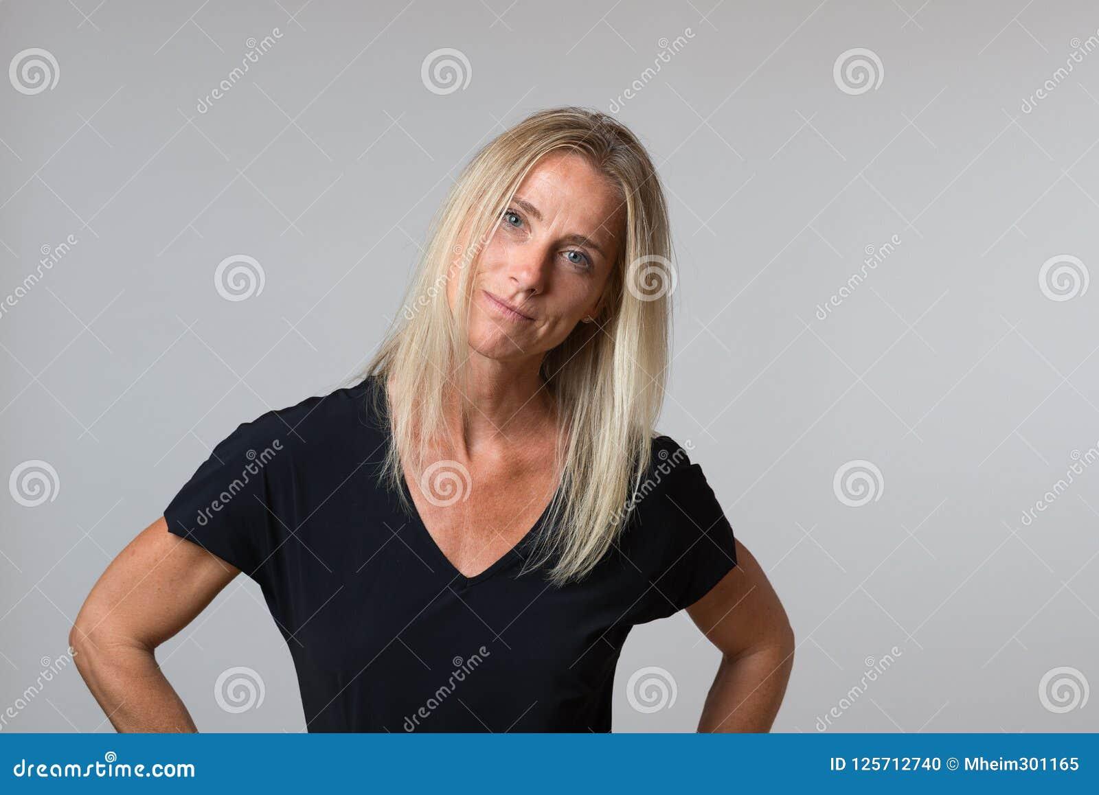 Femme blonde heureuse attirante avec un sourire tranquille