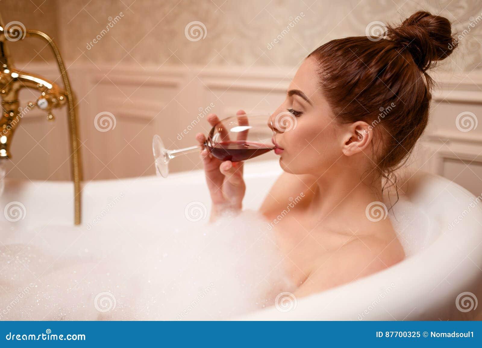Femme buvant du vin rouge dans la baignoire