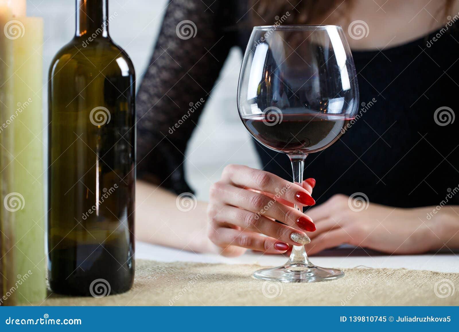 Femme buvant l associé de attente de vin rouge