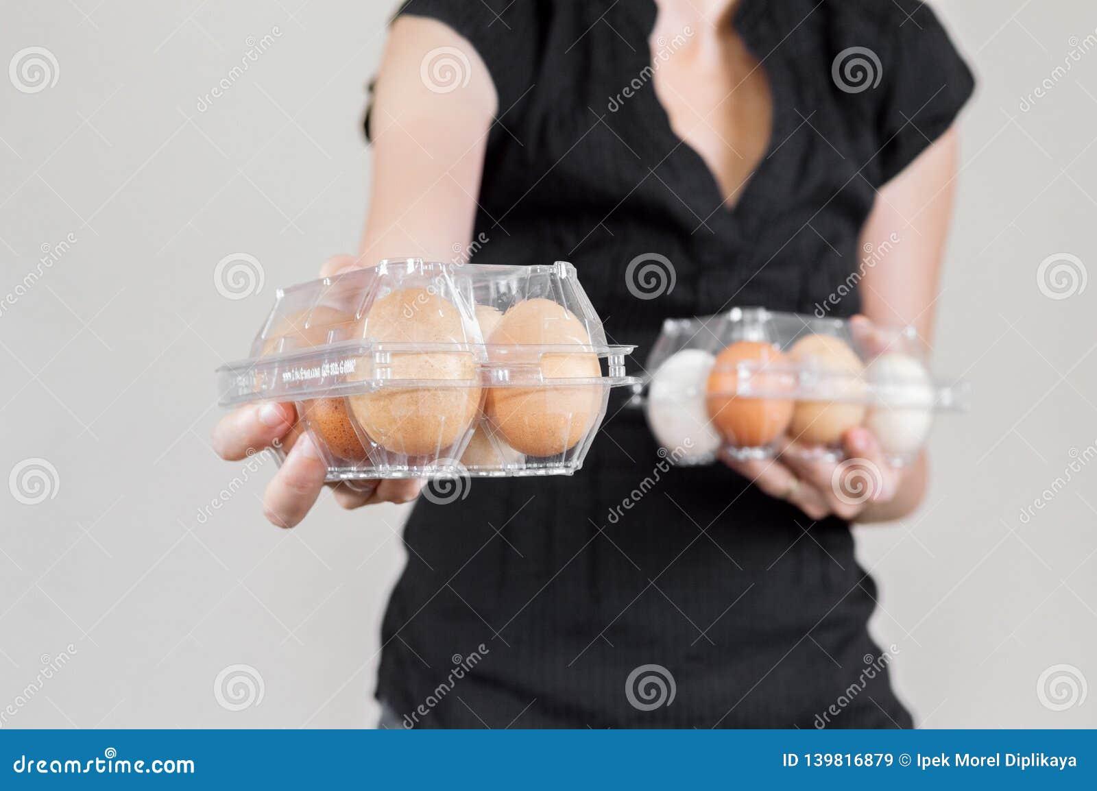 Femme caucasienne avec la chemise noire jugeant deux boîtes à oeufs en plastique pleines des oeufs de poulet