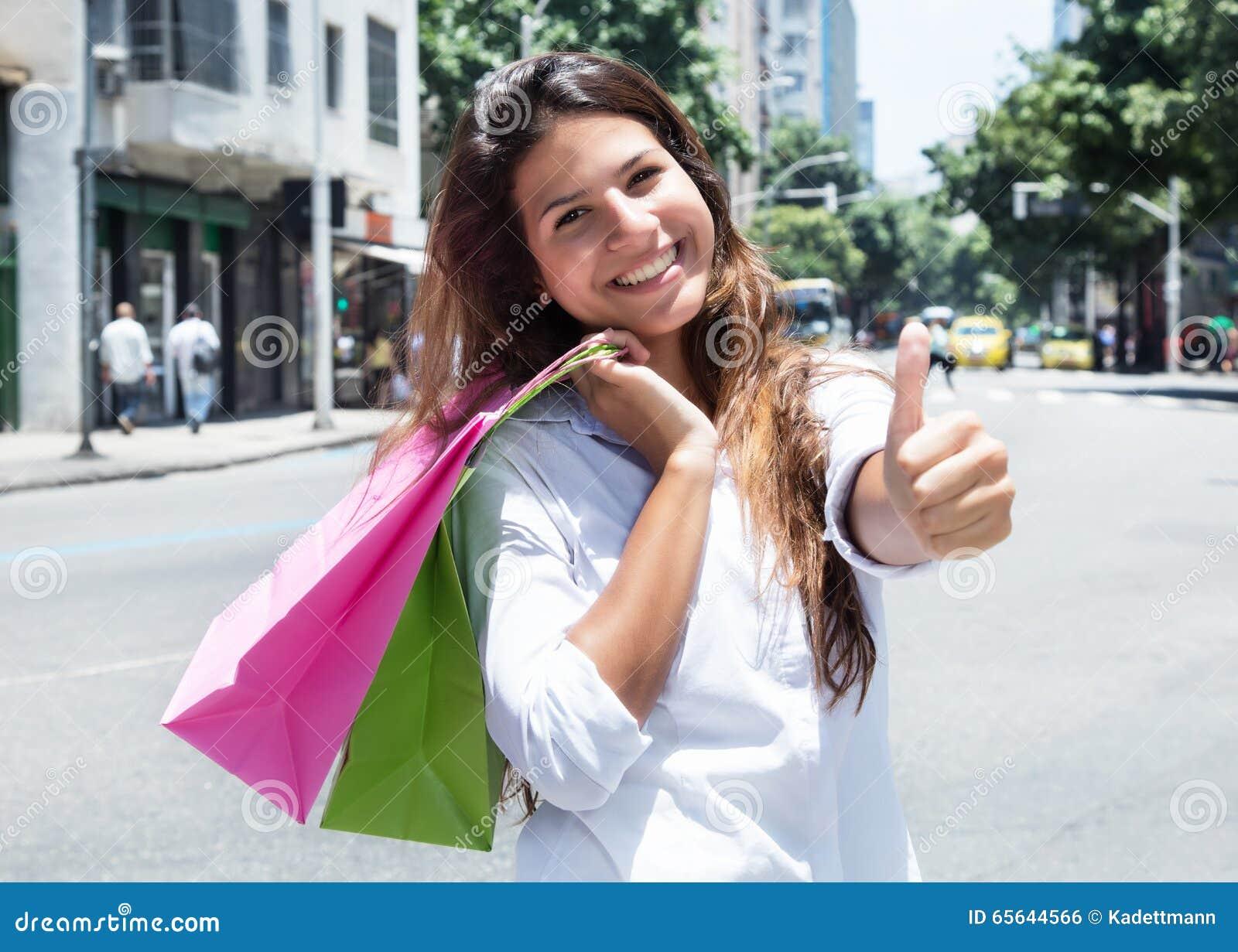 Femme caucasienne heureuse avec des paniers dans la ville