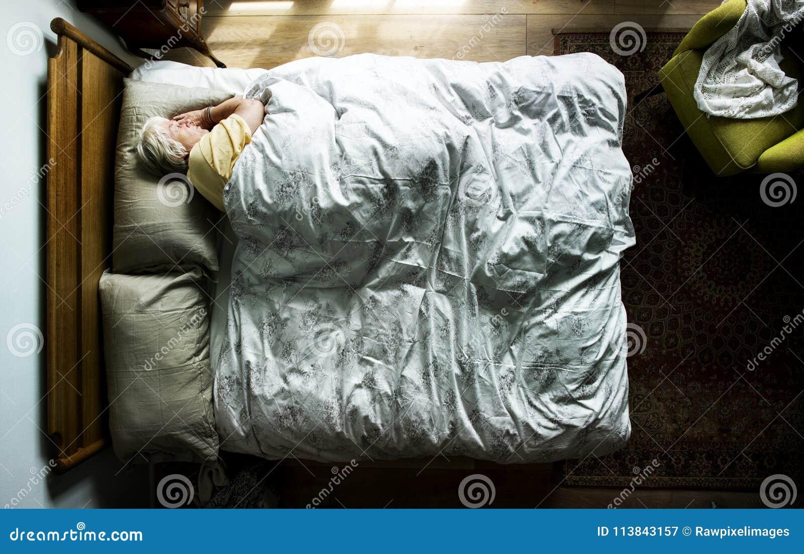Femme caucasienne pluse âgé dormant sur le lit