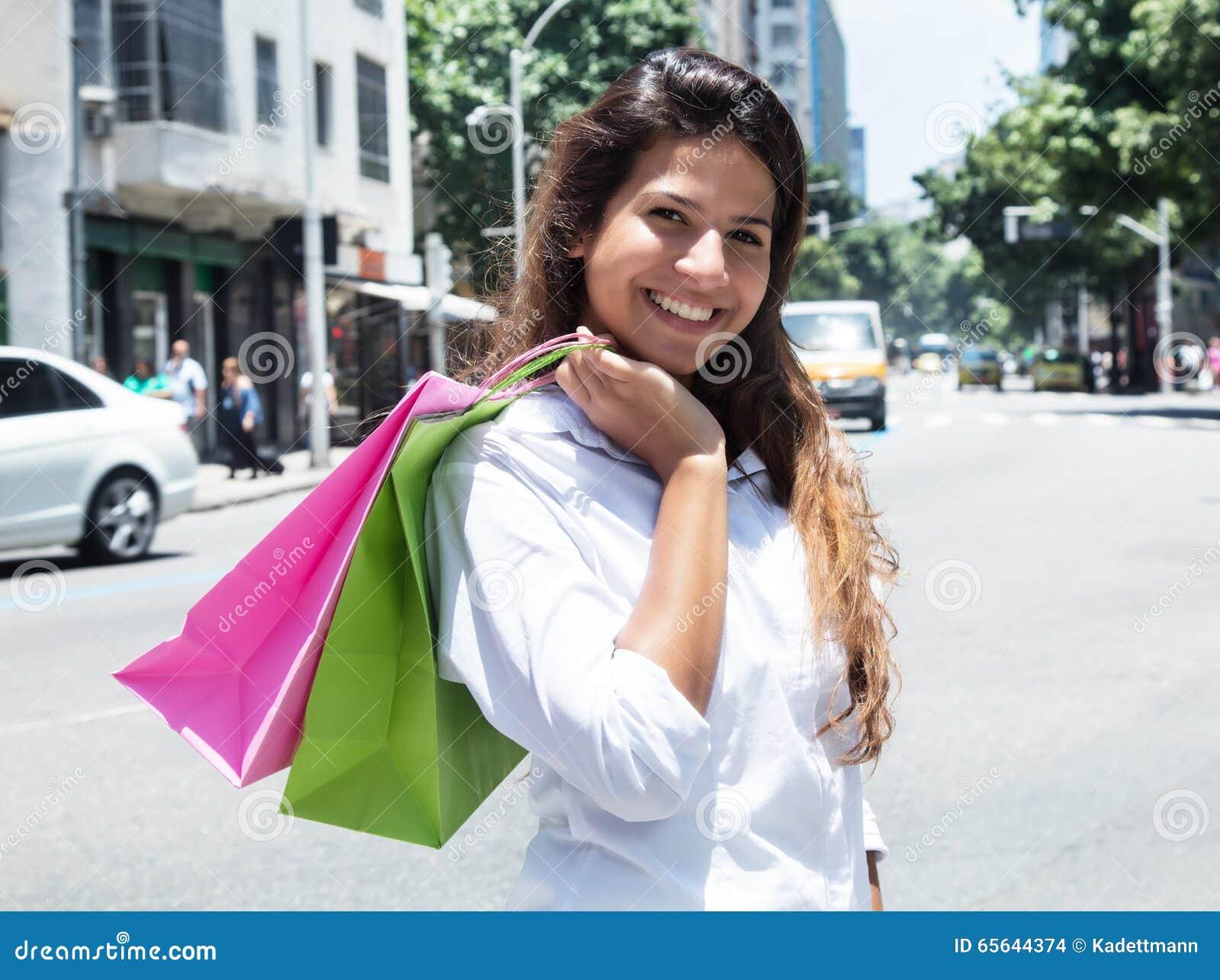 Femme caucasienne riante avec des paniers dans la ville