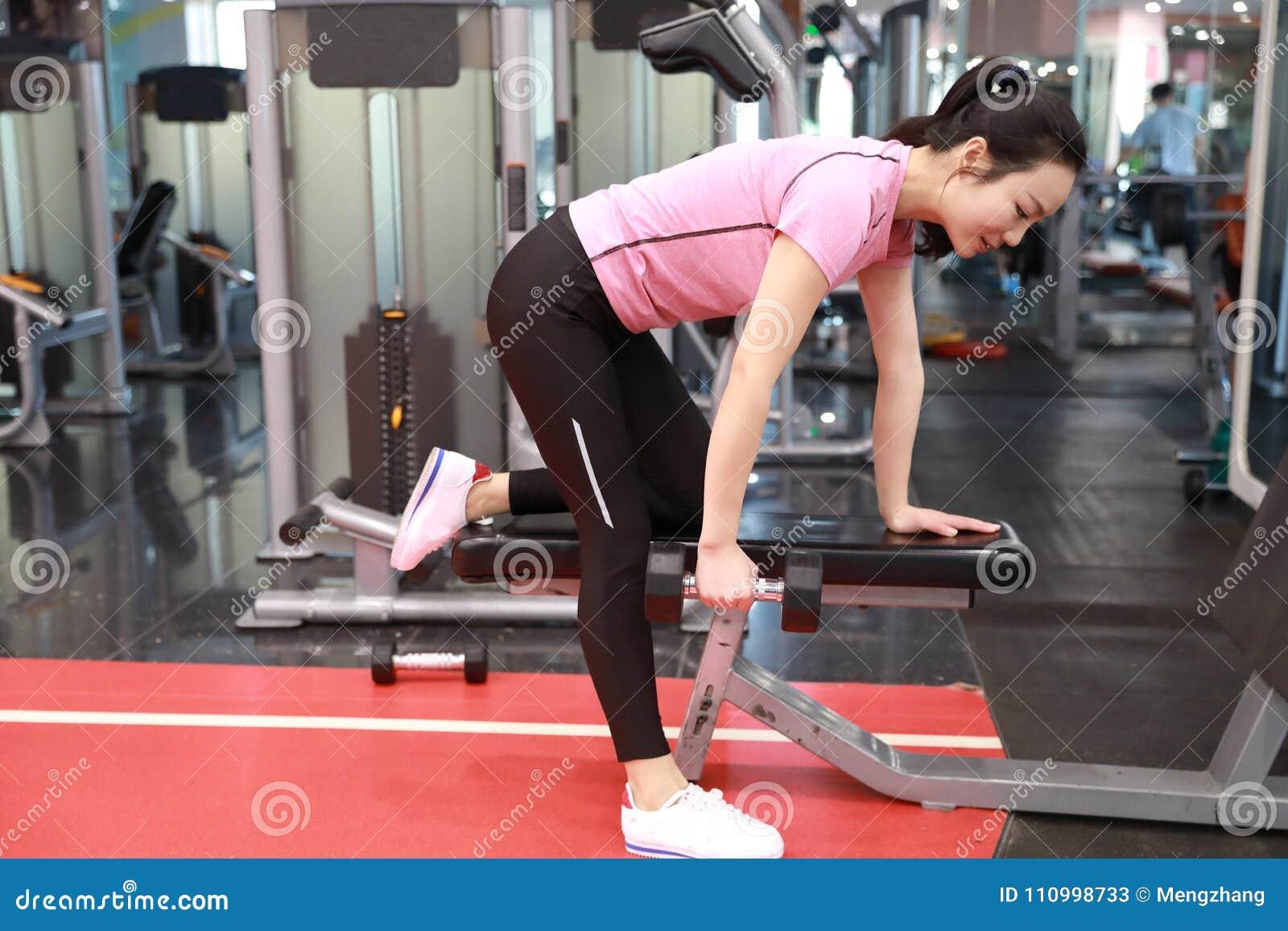 Femme chinoise asiatique dans fille de ŒFitness de ¼ d ï de gymnase la jeune dans le gymnase faisant des exercices avec des haltè