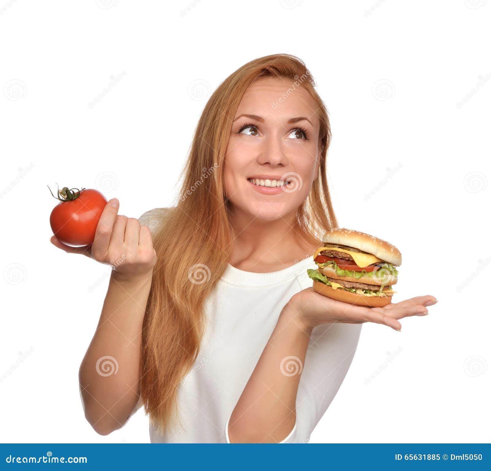 Femme comparant le sandwich malsain savoureux à hamburger à disposition et le toma