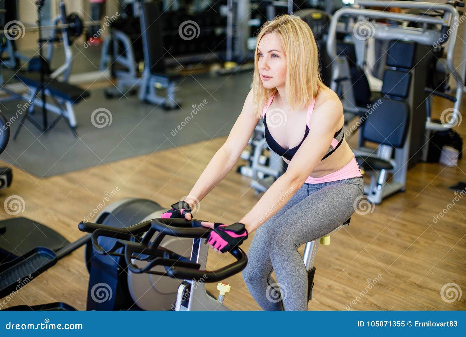 Femme convenable établissant sur le vélo d exercice au gymnase Tir d intérieur d une formation faisante femelle de forme physique