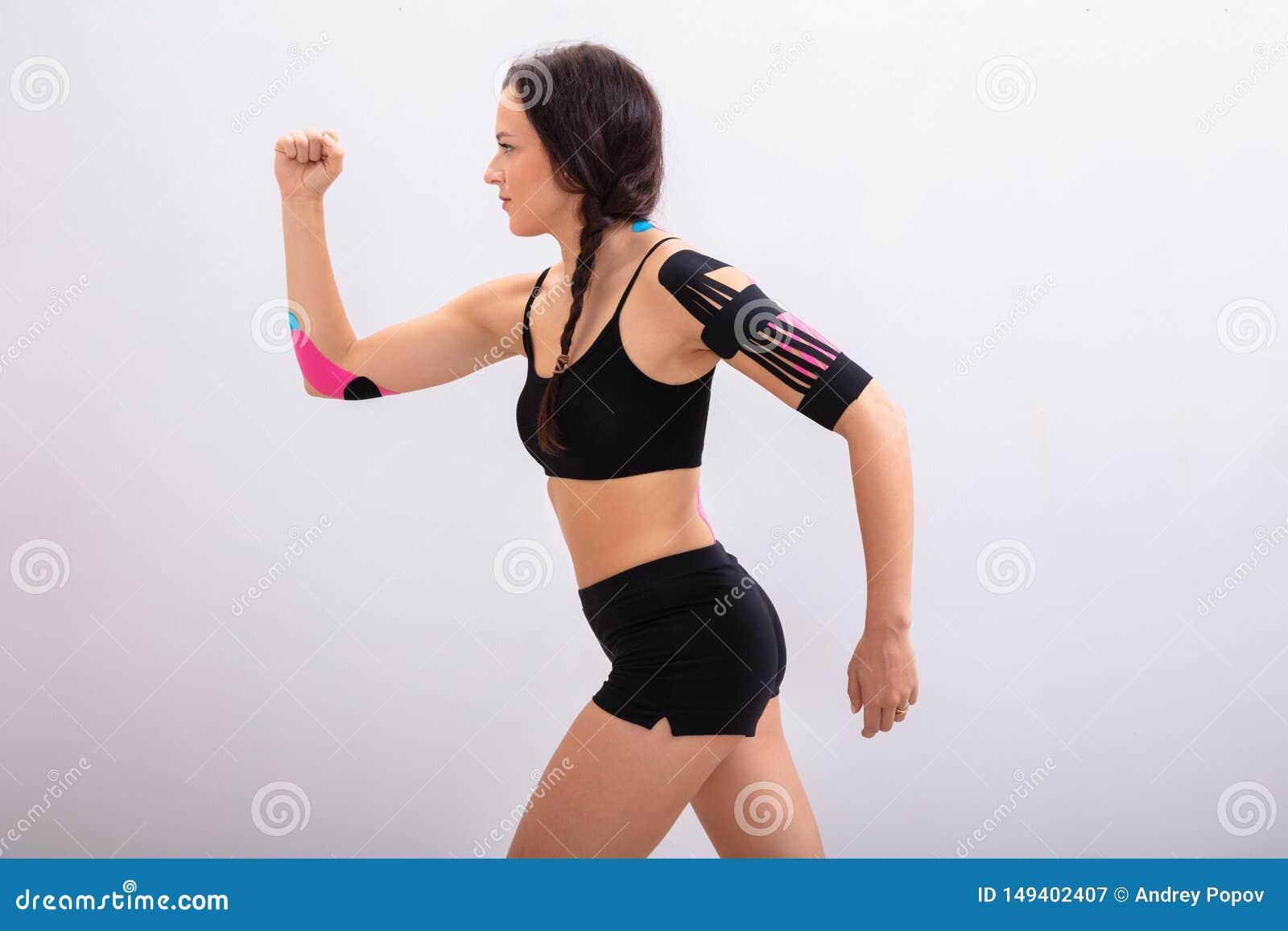 Femme courant avec la physio- bande sur son corps