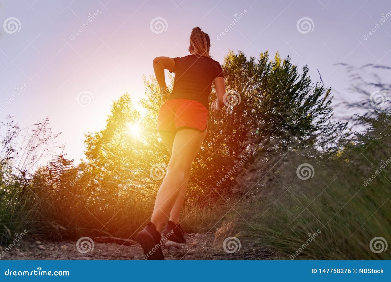 Femme courant dans les montagnes au coucher du soleil