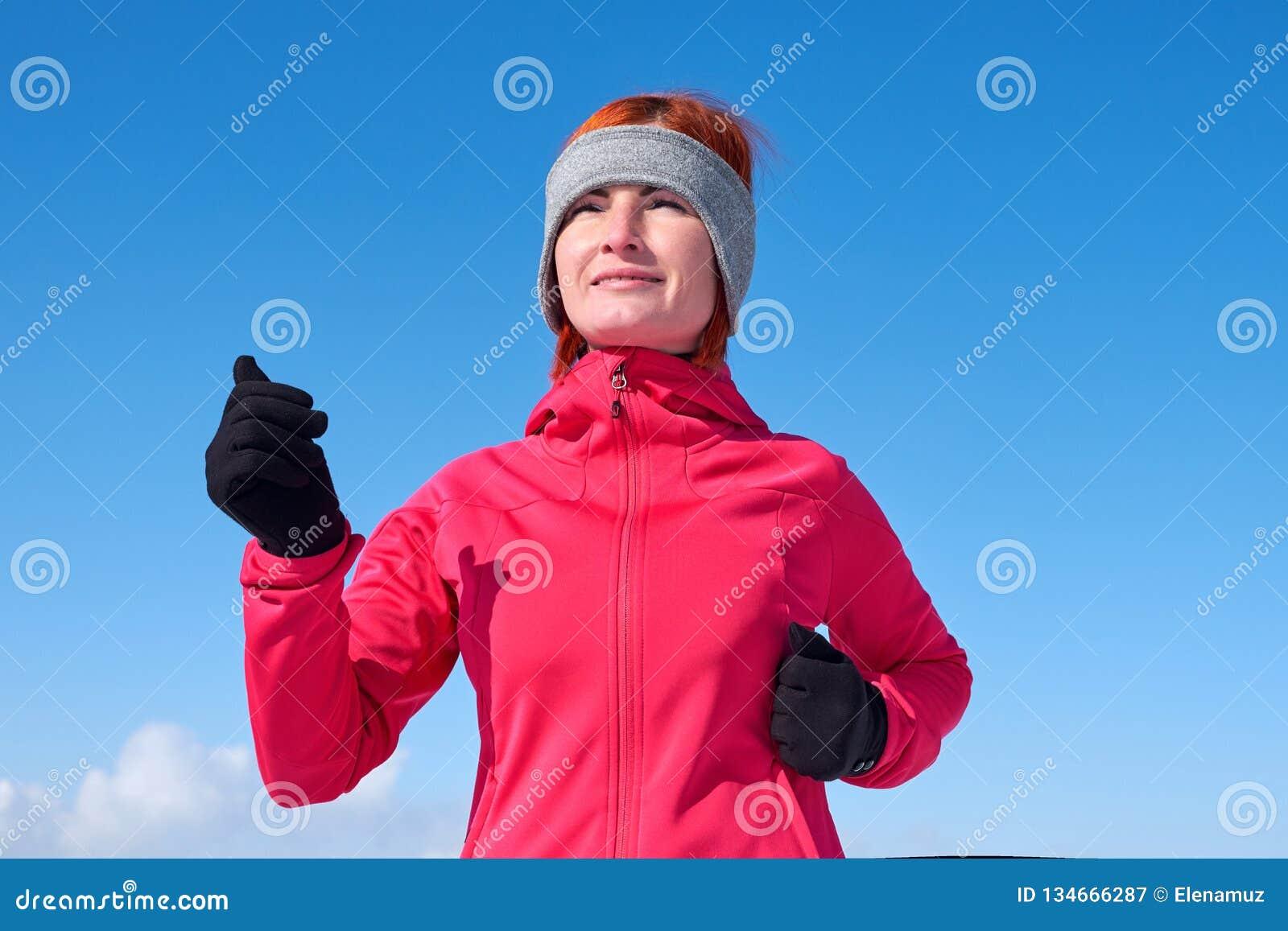 Femme courante d athlète sprinting pendant la formation de l hiver à l extérieur par temps froid de neige Fermez-vous vers le hau