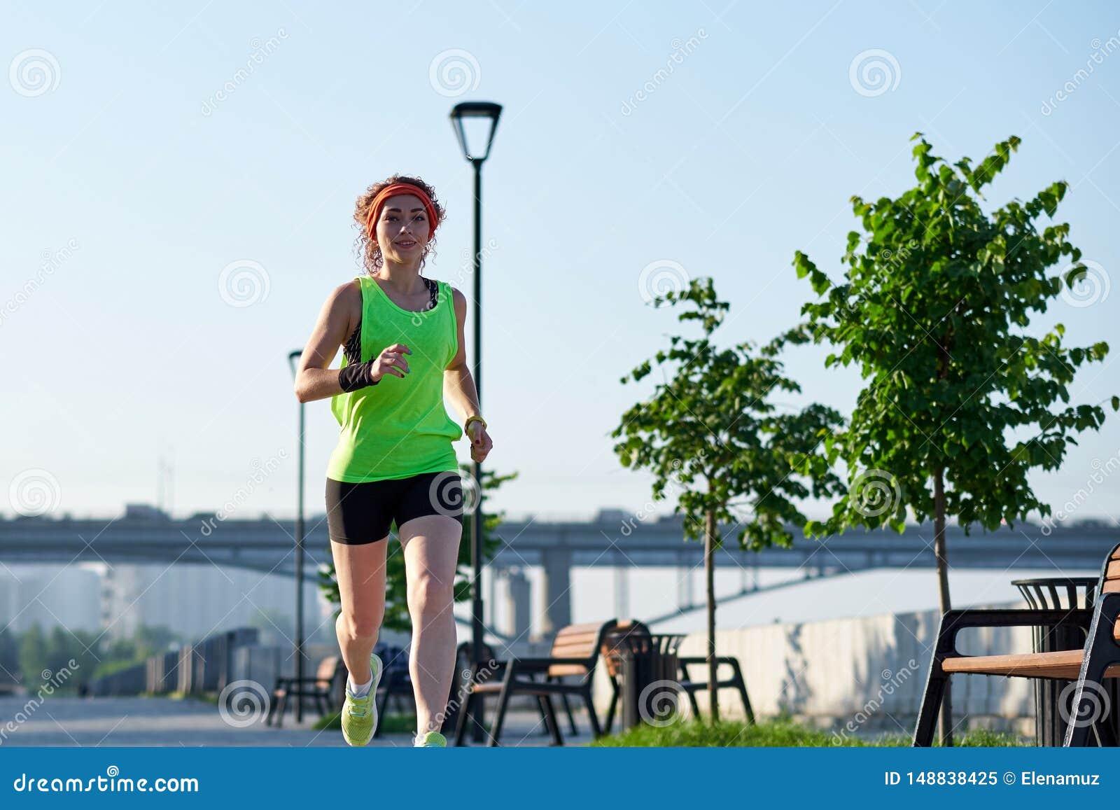 Femme courante sur le bord de mer Pulser de matin Les trains d athl?te