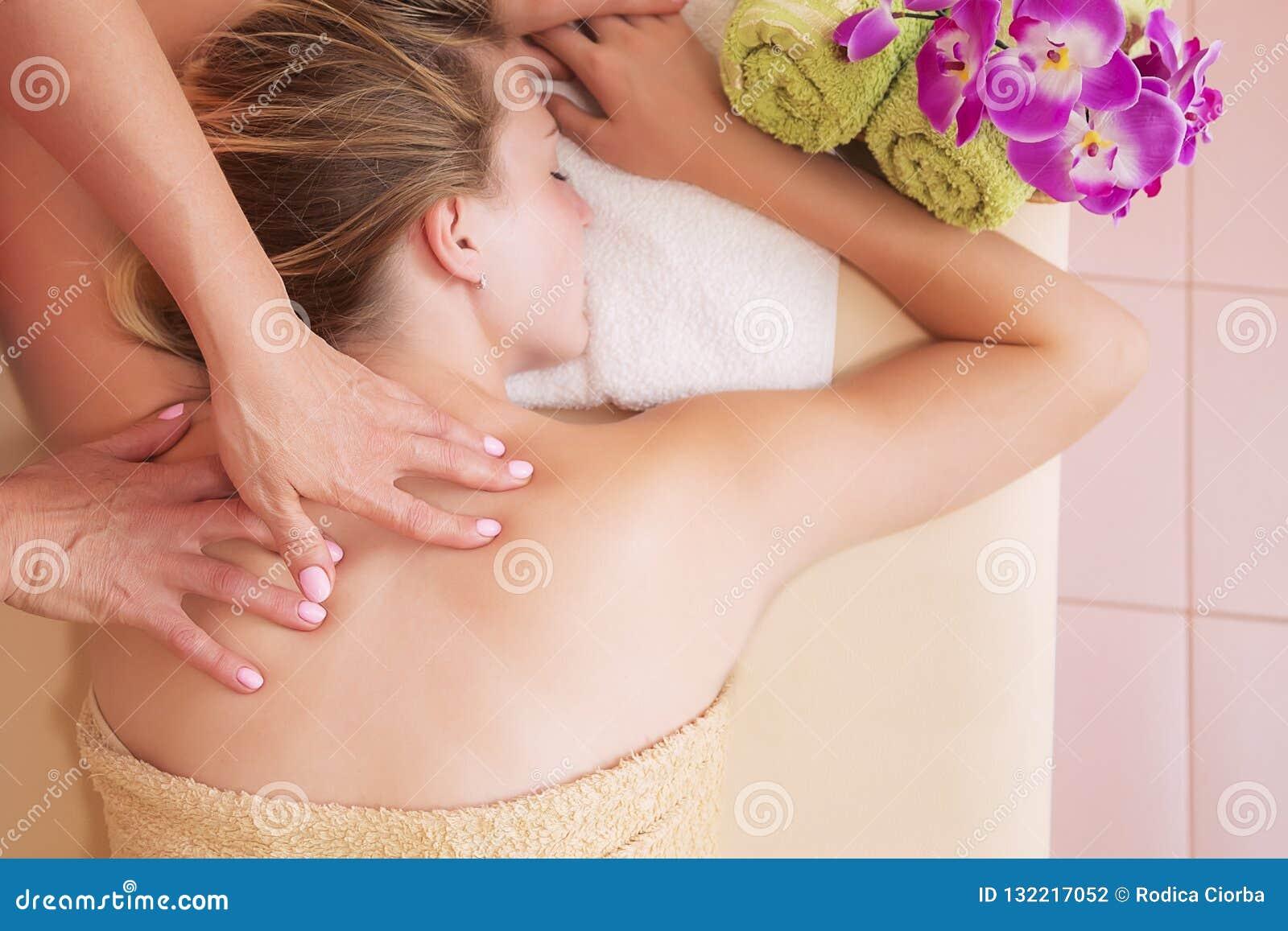 Femme décontractée sur la table de massage recevant le traitement de beauté à la station thermale de jour