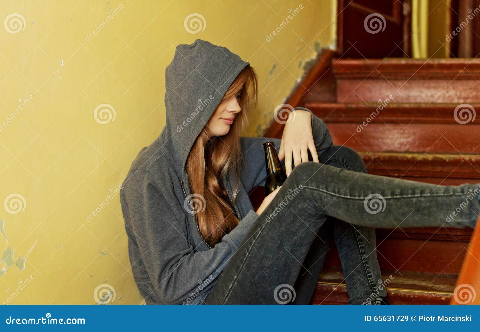 Femme déprimée adolescente s asseyant sur l escalier et buvant d une bière