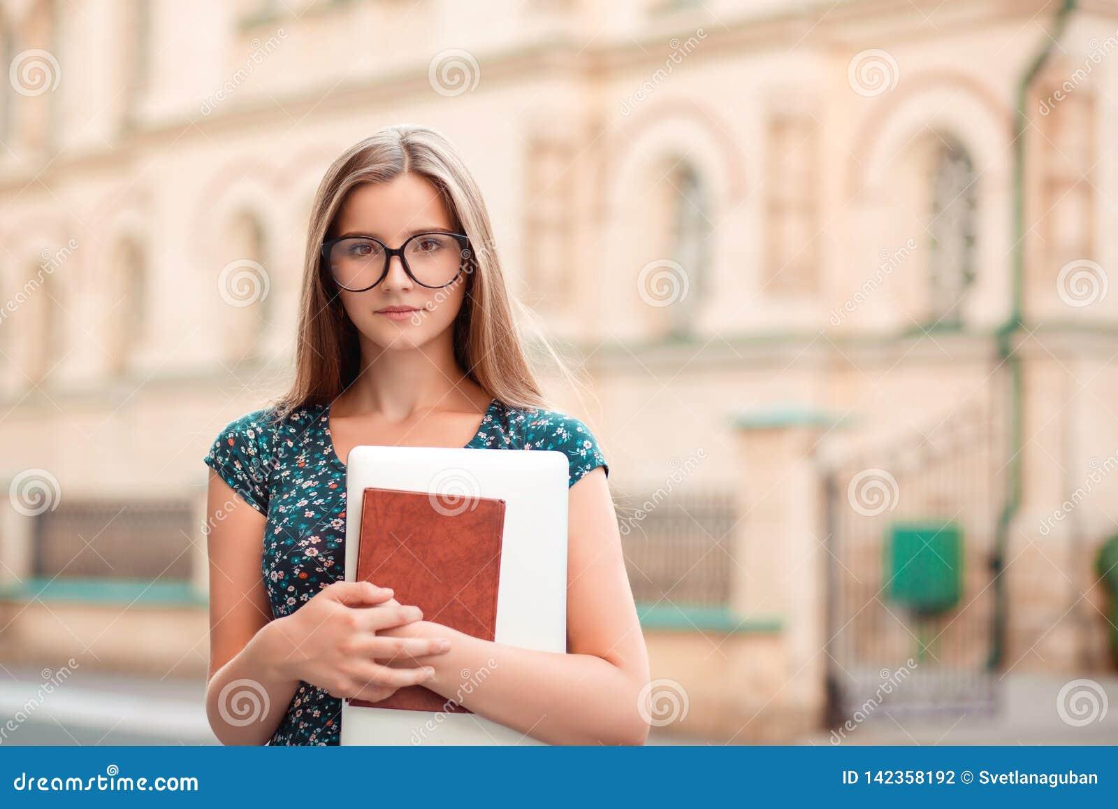 Femme d ?tudiant tenant l ordinateur portable de PC de livres semblant s?r