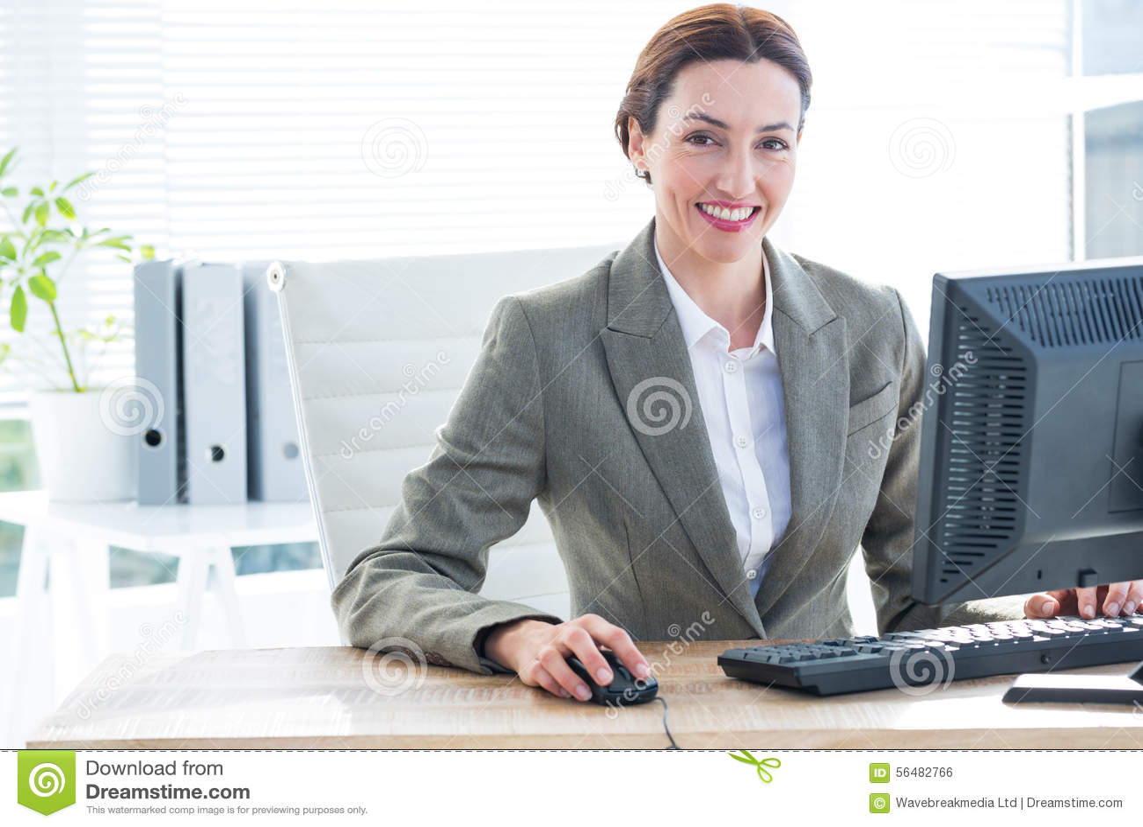 Femme d affaires à l aide de l ordinateur et souriant à l appareil-photo