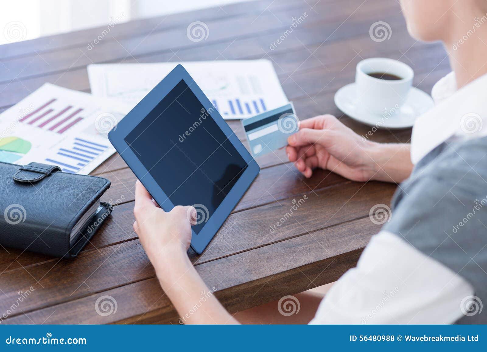 Femme d affaires à l aide du PC de comprimé et tenant la carte de crédit