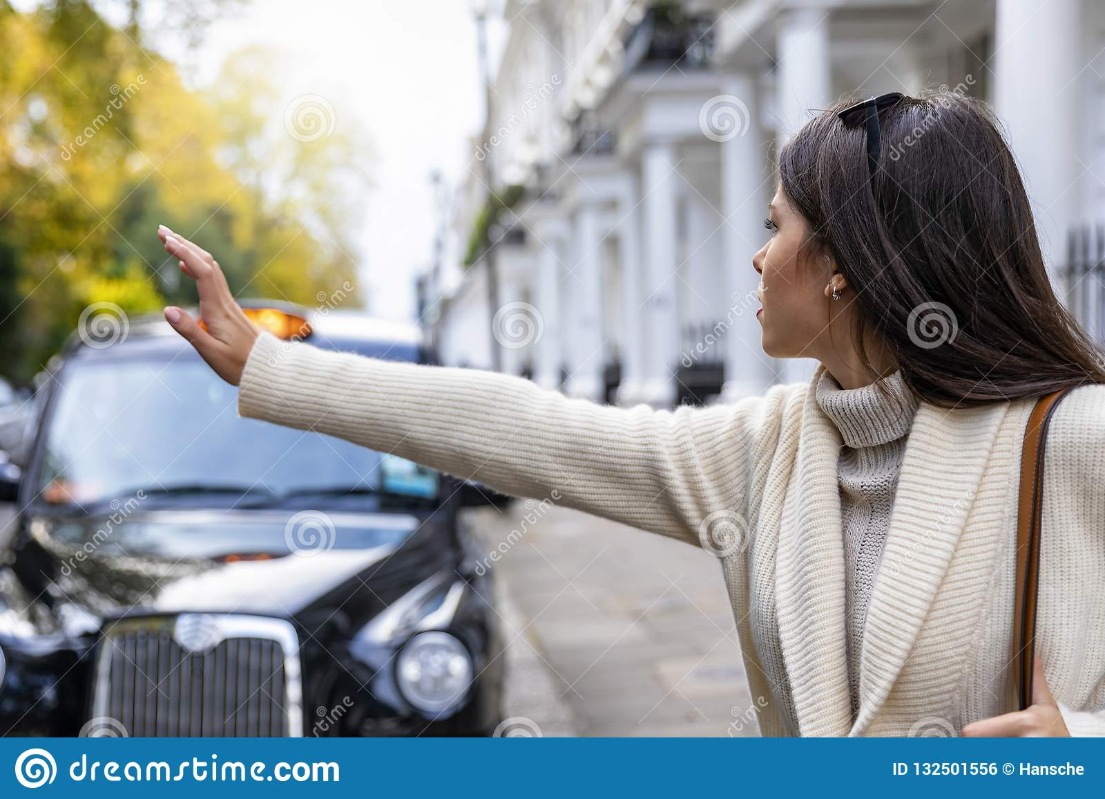 Femme d affaires à Londres grêlant pour un taxi noir