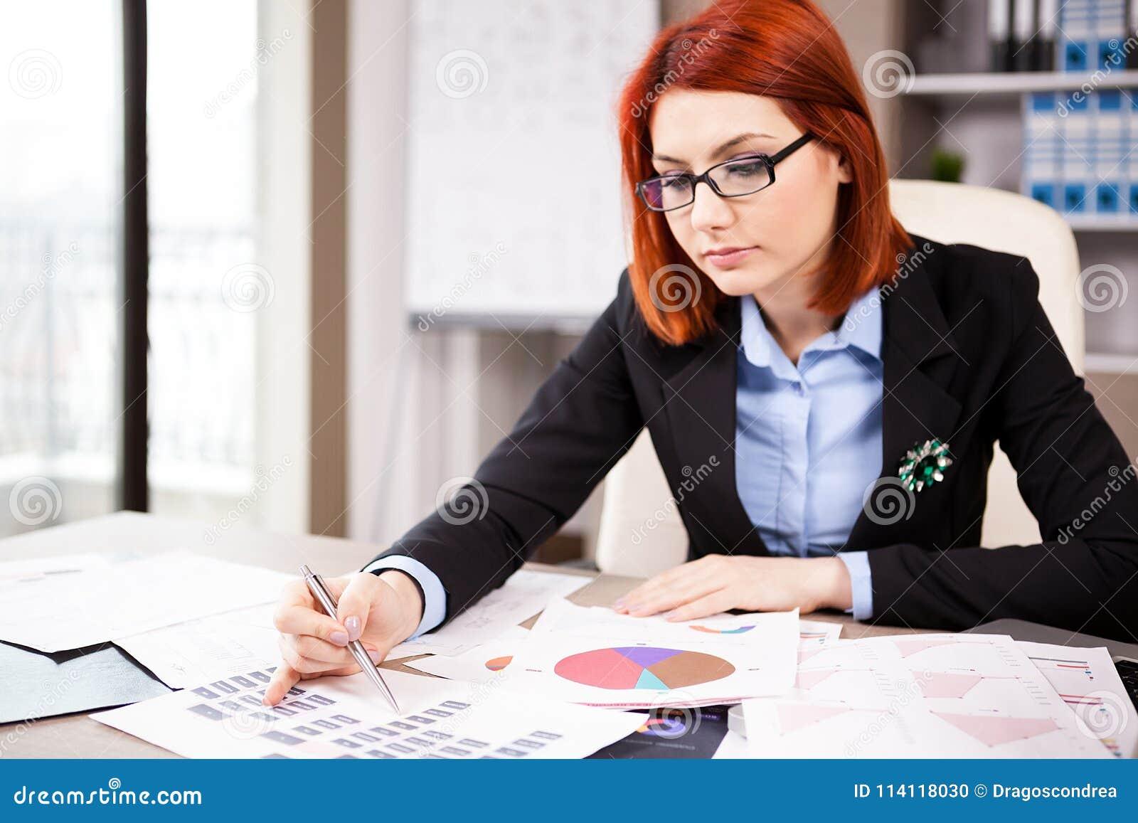 Femme d affaires à sa table regardant des diagrammes