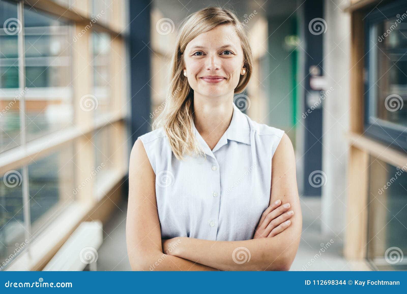 Femme d affaires authentique blonde avec le sourire croisé de bras