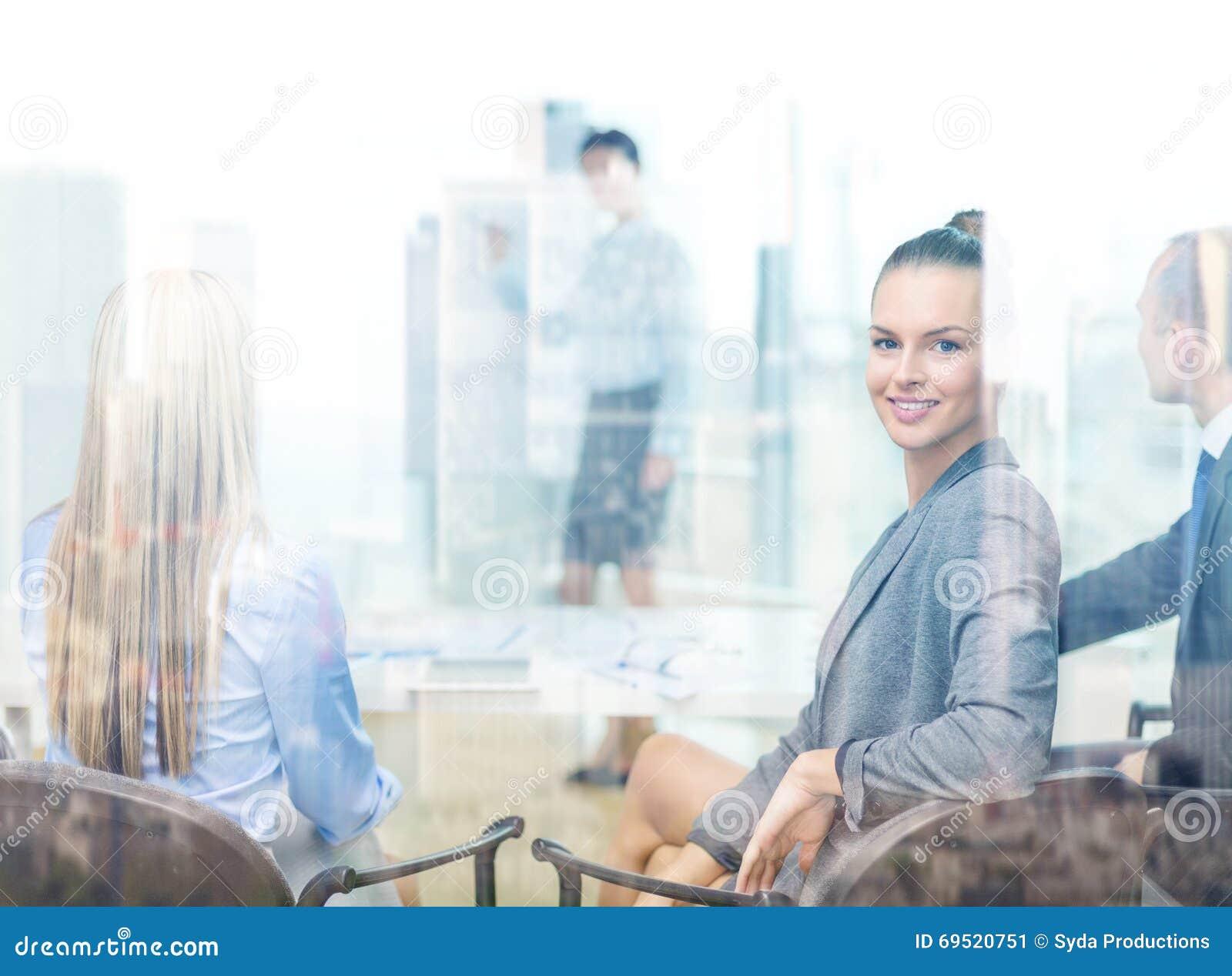 femme d 39 affaires avec l 39 quipe montrant dans le bureau photo stock image 69520751. Black Bedroom Furniture Sets. Home Design Ideas
