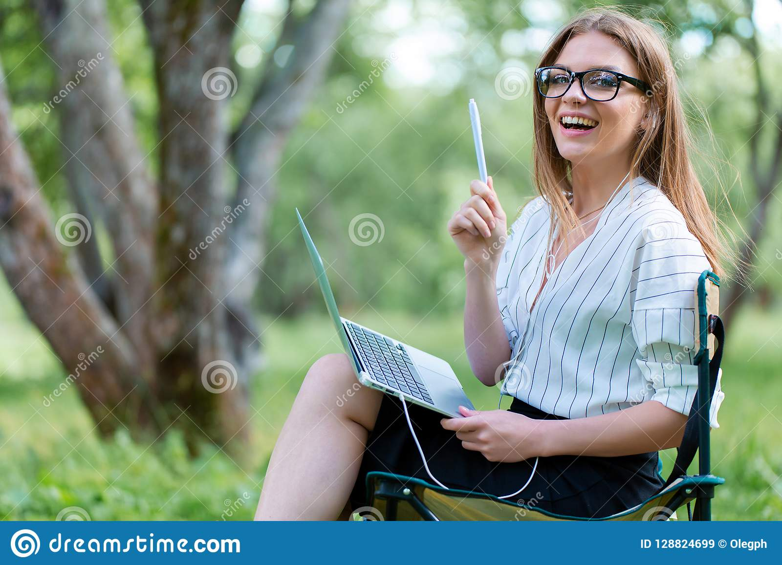 Femme d affaires avec un ordinateur portable se reposant en parc sur un pliage ch