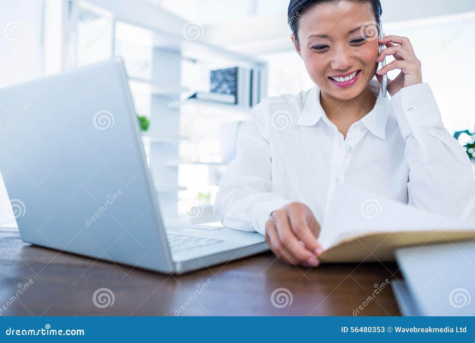 Femme d affaires ayant l appel téléphonique et regardant des documents