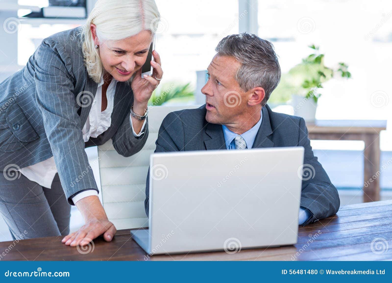 Femme d affaires ayant l appel téléphonique et regardant l ordinateur portable