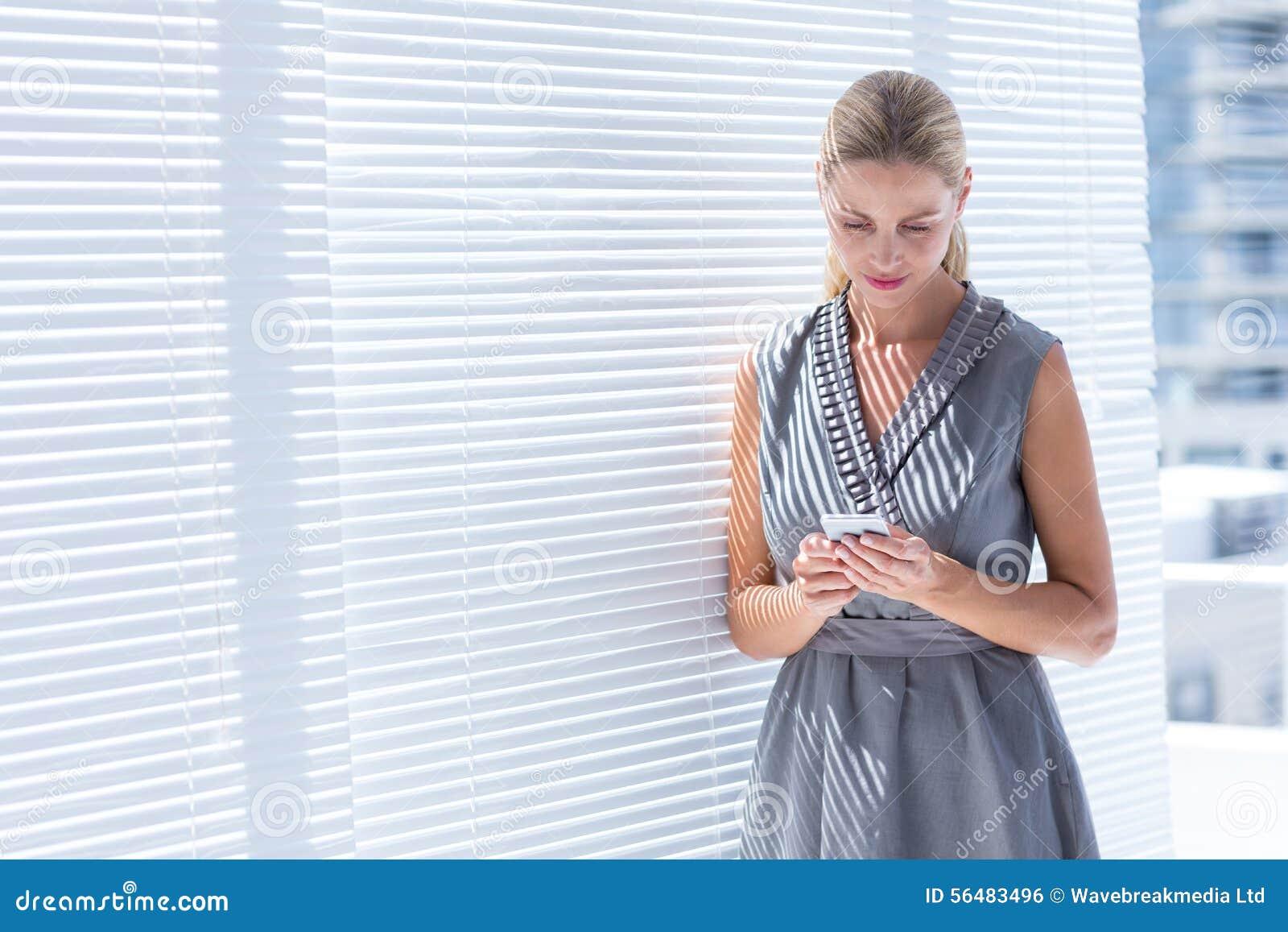 Femme d affaires concentrée envoyant un message textuel