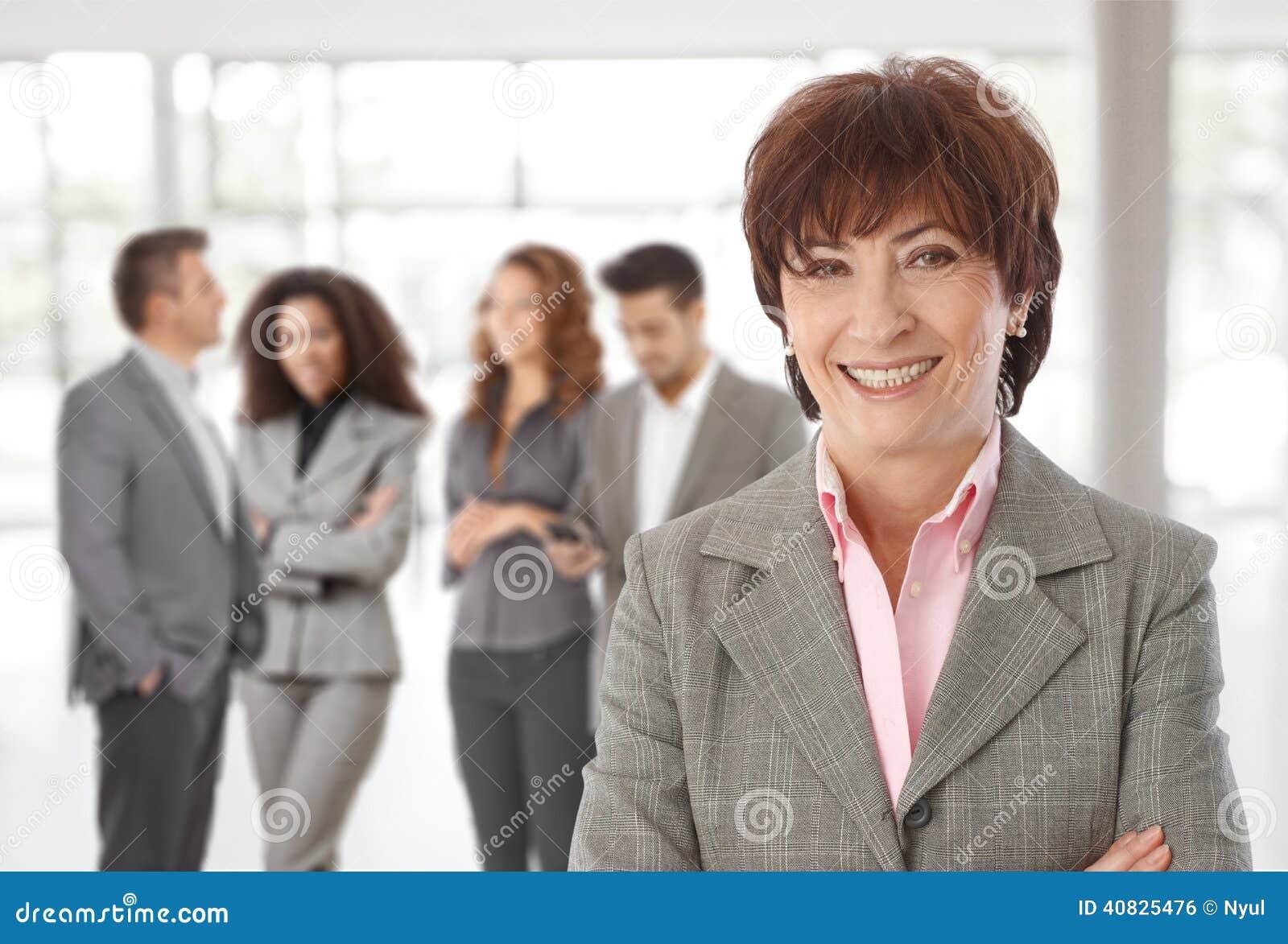 femme d 39 affaires d 39 une cinquantaine d 39 ann es devant des coll gues photo stock image 40825476. Black Bedroom Furniture Sets. Home Design Ideas
