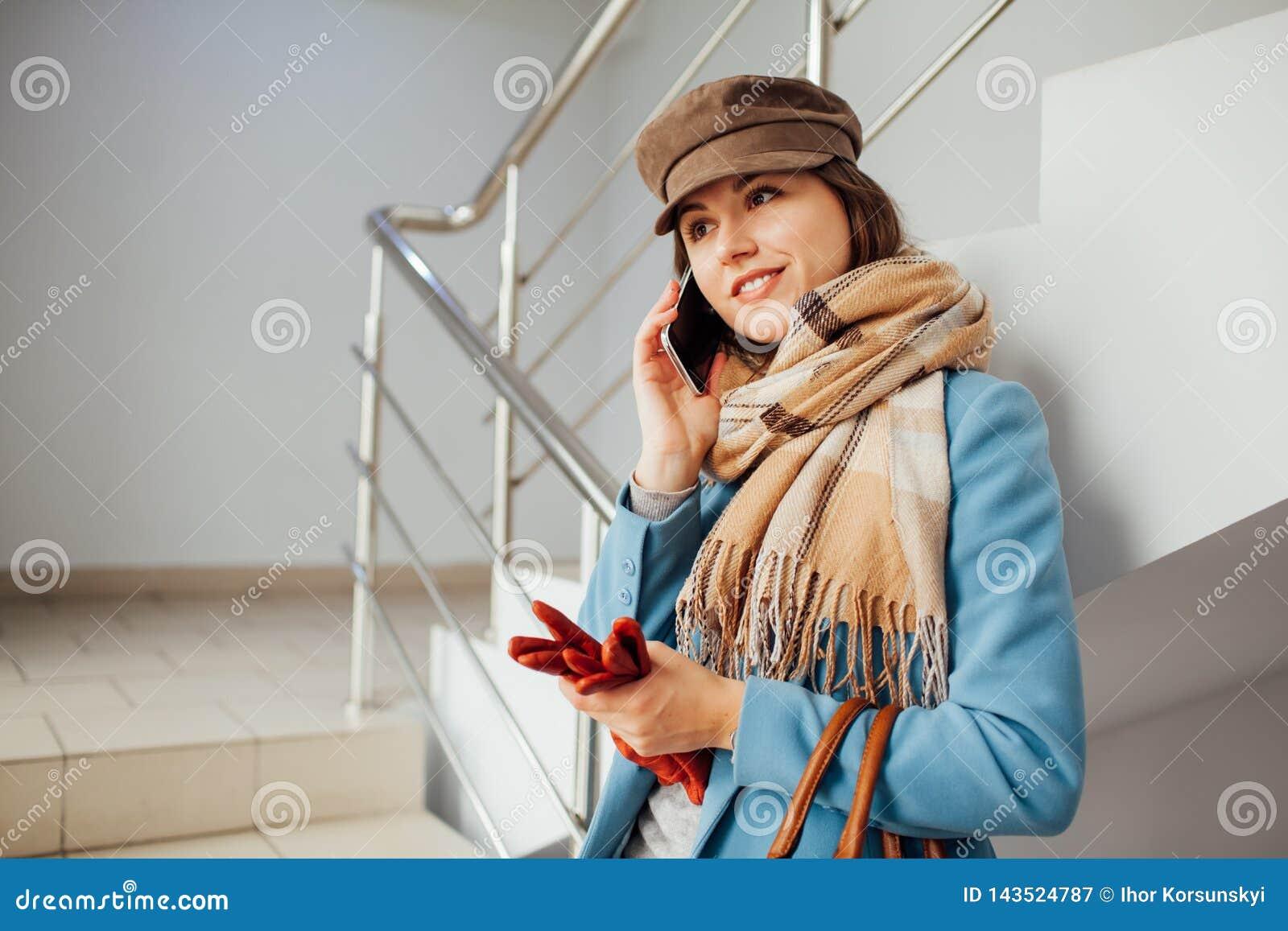 Femme d affaires dans des supports de manteau sur les escaliers dans le mail avec le smartphone Achats Mode