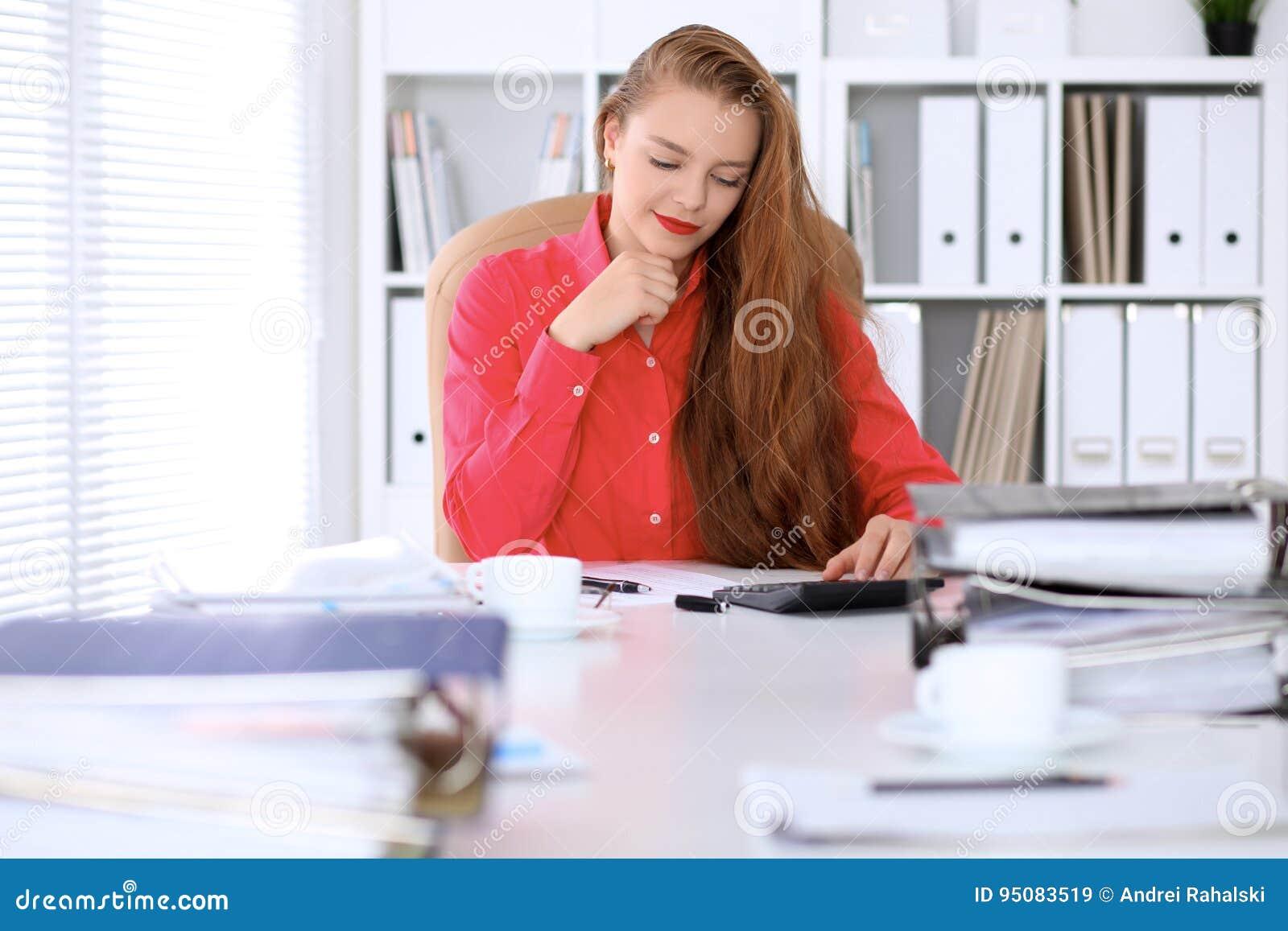 Femme d affaires dans le chemisier rouge rédigeant le rapport, calculant ou vérifiant l équilibre