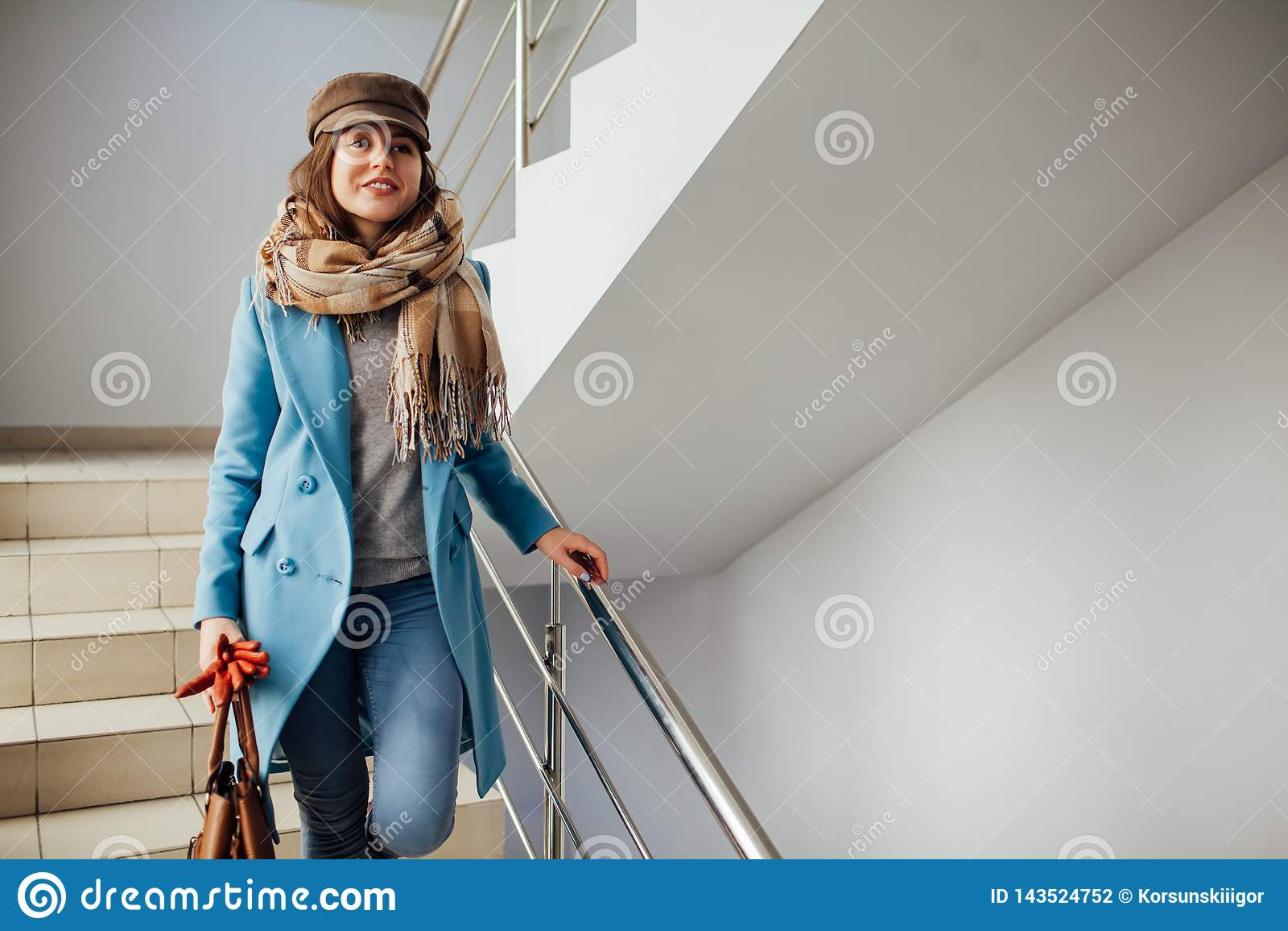 Femme d affaires dans le manteau descendant les escaliers dans le mail Achats Mode