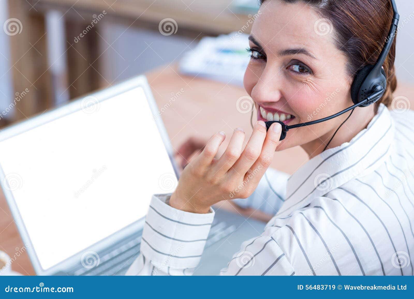 Femme d affaires de brune à l aide de l ordinateur portable et de l écouteur