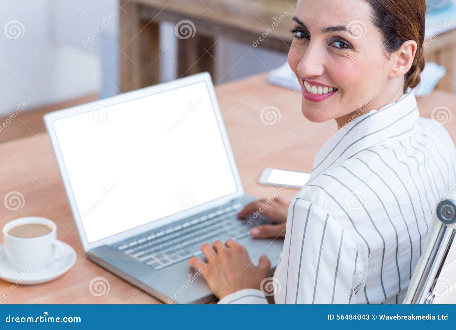 Femme d affaires de brune souriant utilisant l ordinateur portable