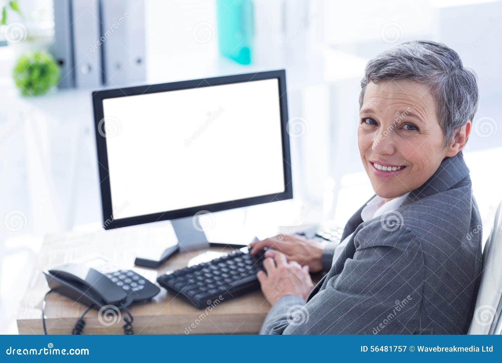 Femme d affaires de sourire à l aide de l ordinateur