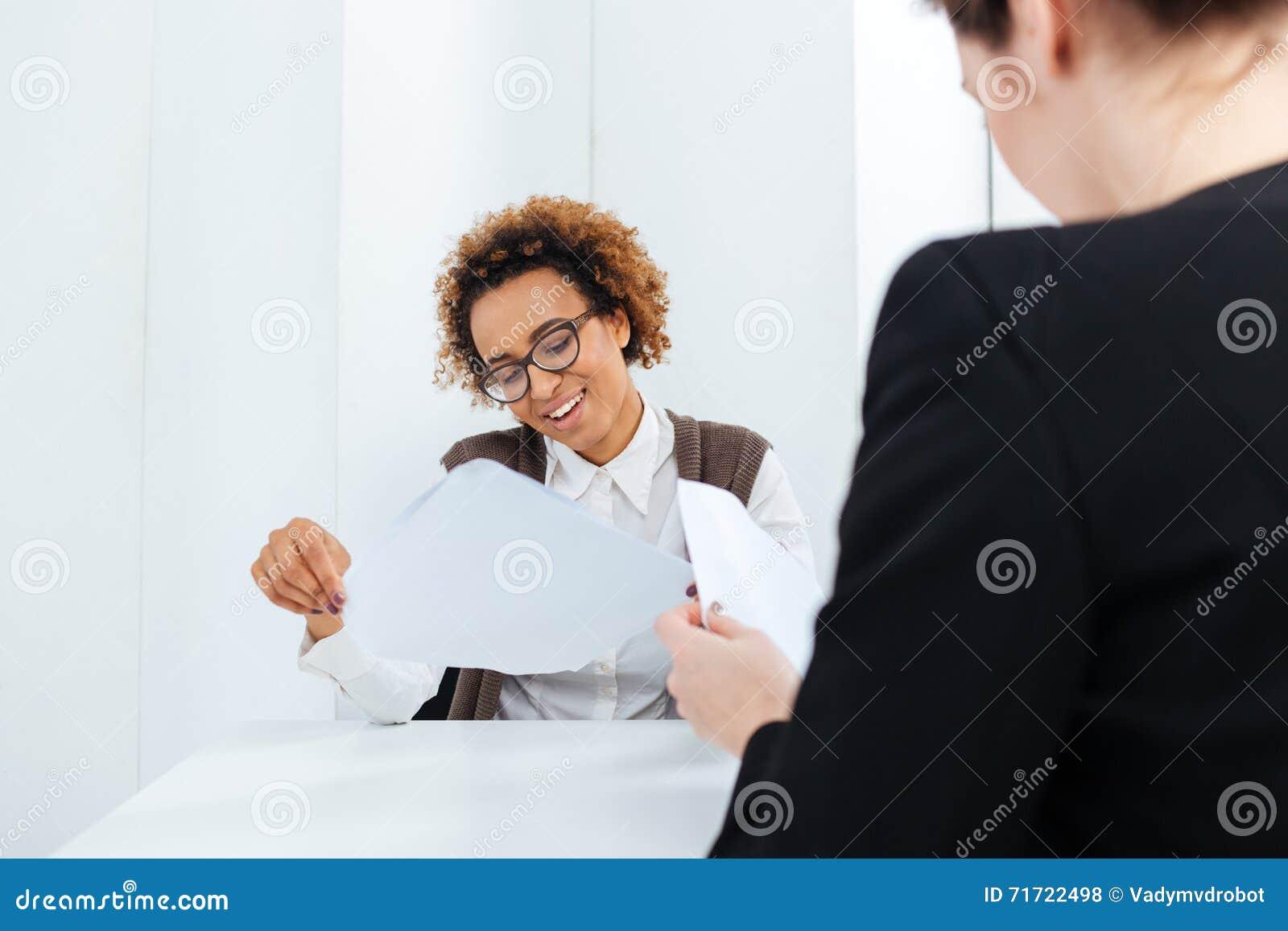 Femme d affaires de sourire d afro-américain ayant l application d entrevue d emploi et de remplir